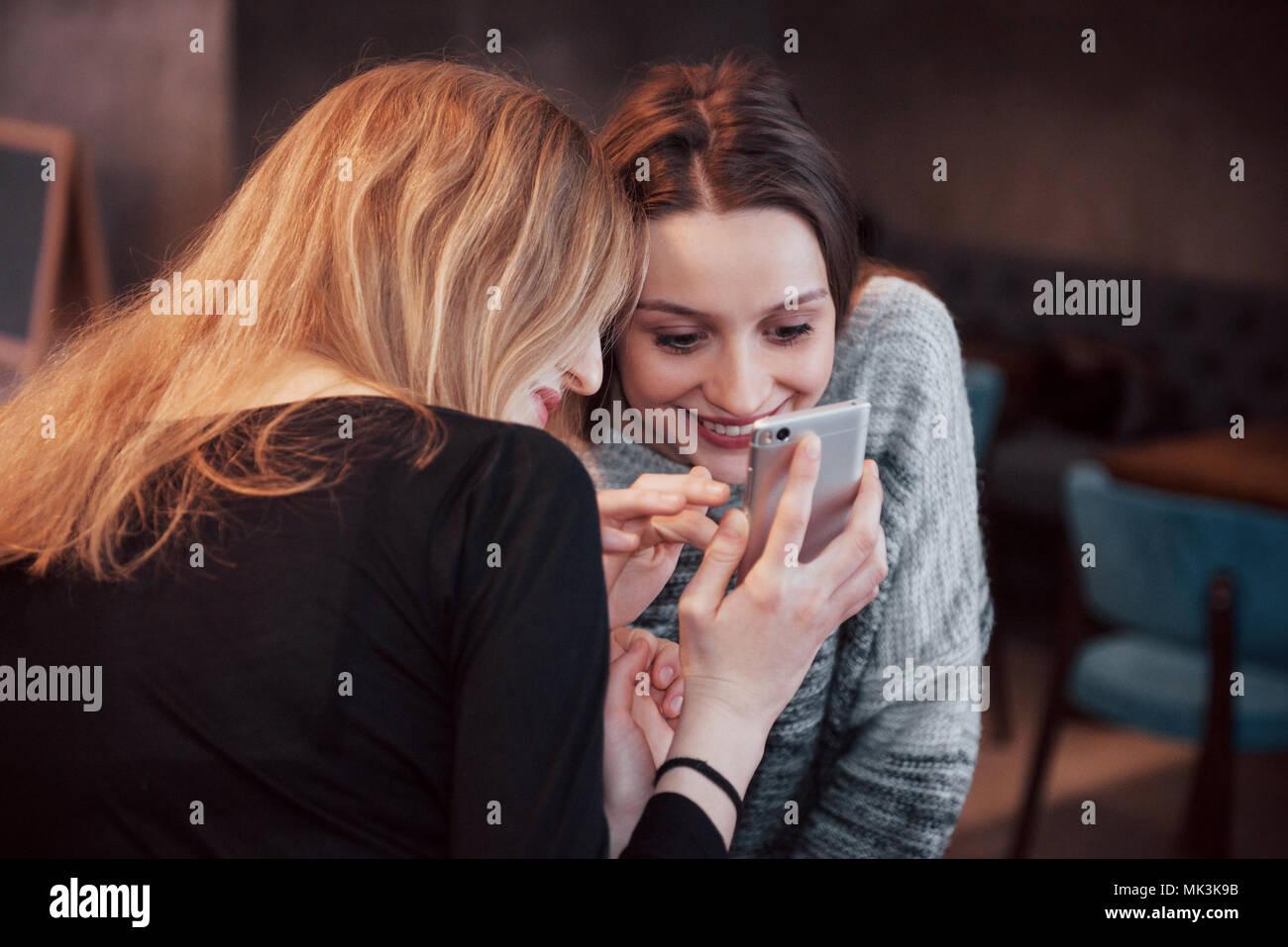 Dos sonriendo amigos leer funny chat sobre teléfono moderno sentado con sabroso café en el restaurante.Hipster niñas disfrutando de tiempo de recreo en la cafetería con bebidas calientes y mensajería en teléfonos Imagen De Stock
