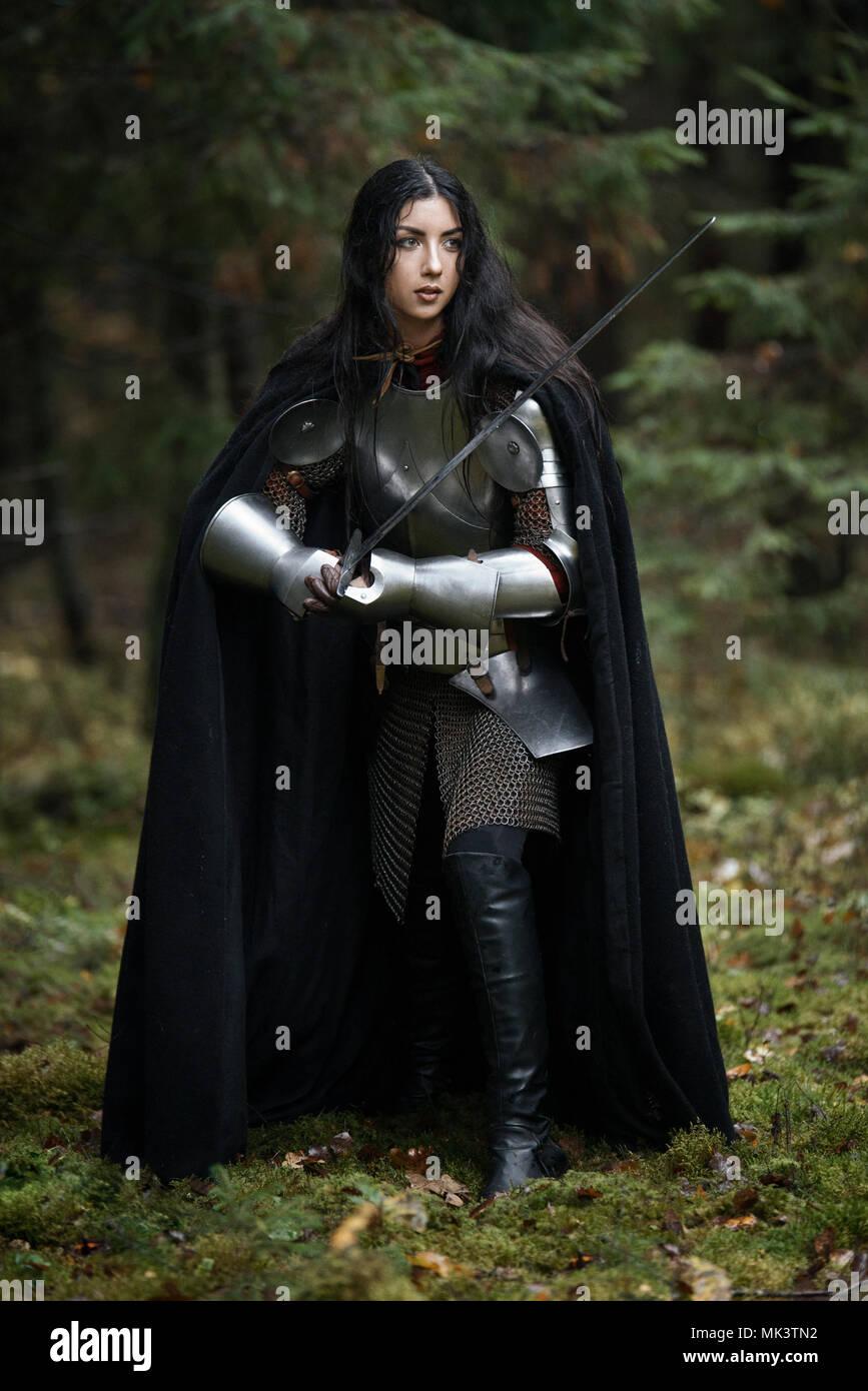 Una hermosa niña de guerrero con una espada vistiendo chainmail y armadura en un misterioso bosque Foto de stock