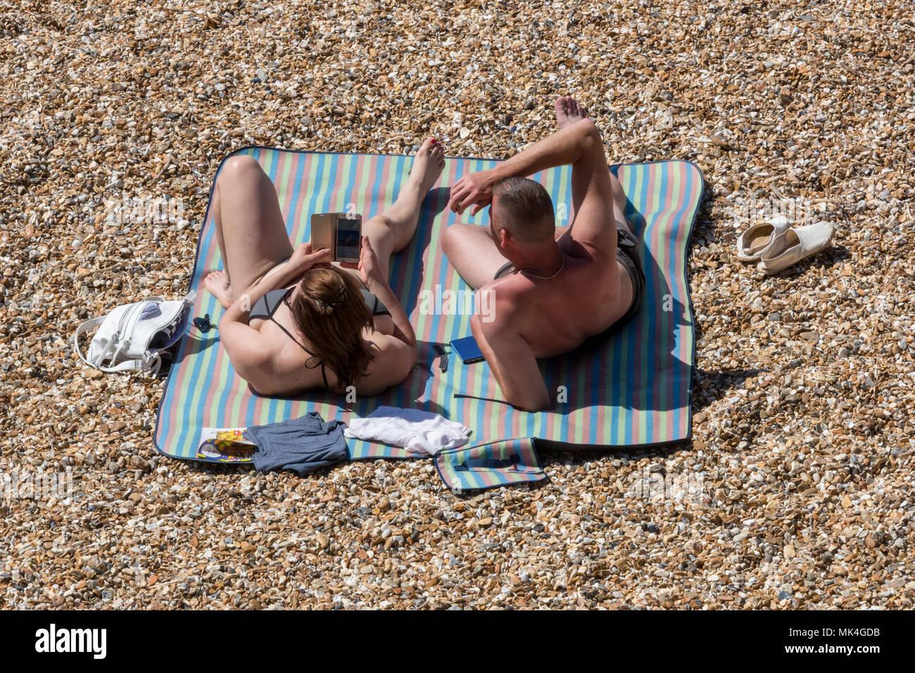 Un hombre y una mujer pareja guijarro o acostado en una playa de guijarros en el sol tomando el sol sobre una toalla stripey. Bañistas exponer su piel a los rayos UV. Imagen De Stock