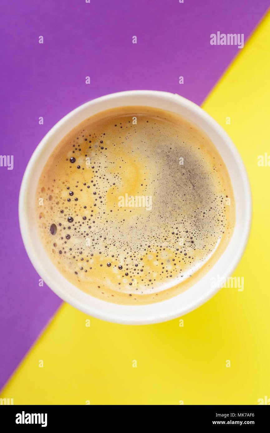 Vista superior de llevar bebida caliente en taza termo abrió en púrpura y fondo amarillo. Cafe crema espuma sobre el café americano Imagen De Stock
