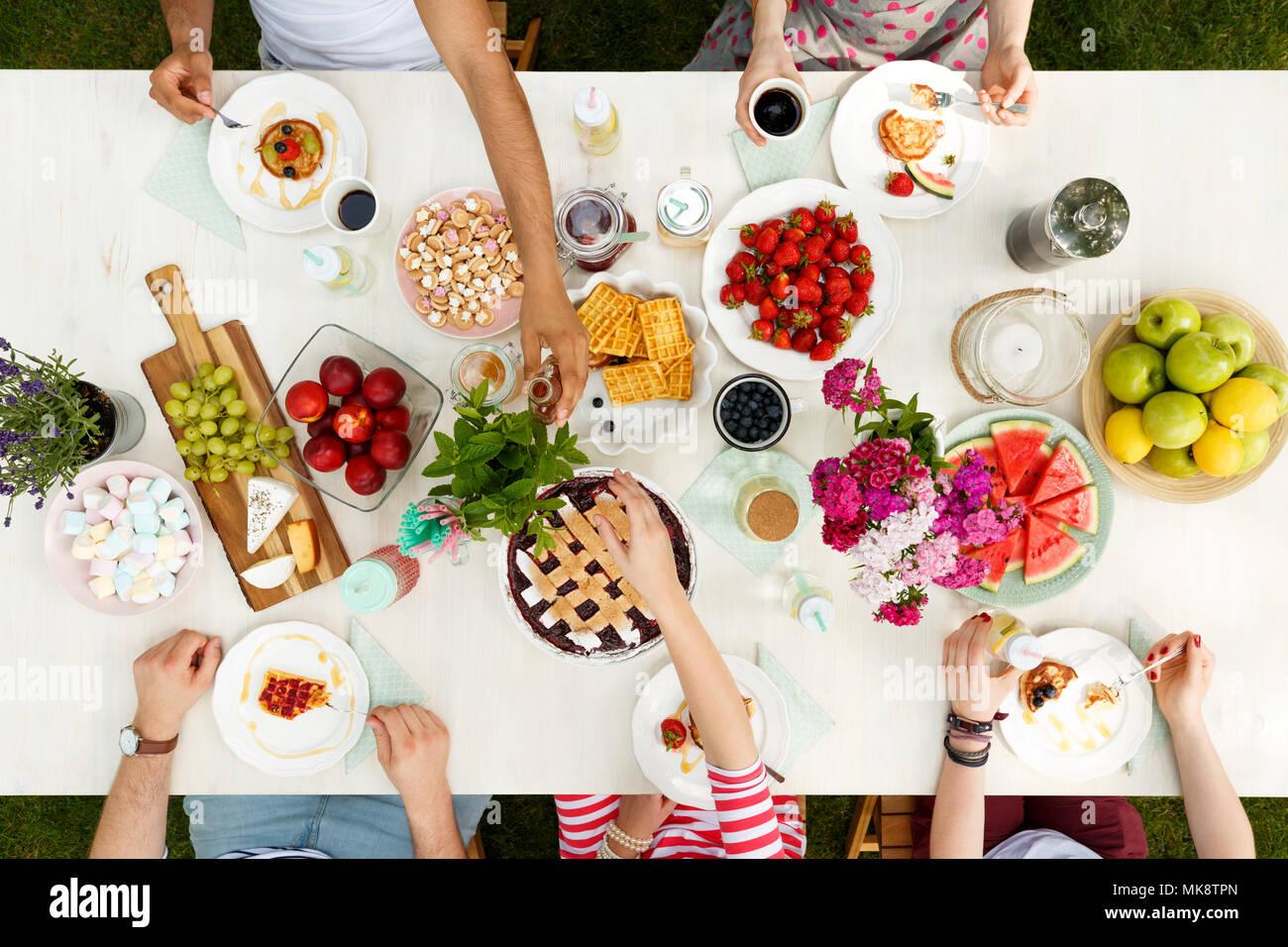 Picnic al aire libre para los jóvenes estudiantes que comparten la comida y comer fruta, pasteles y gofres fuera Imagen De Stock