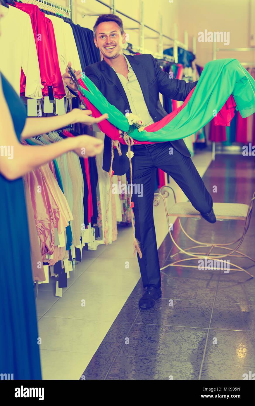 b4b0d7257 Retrato de joven satisfecho hombre vestido de novia ofrece variantes en la  tienda de ropa de la mujer