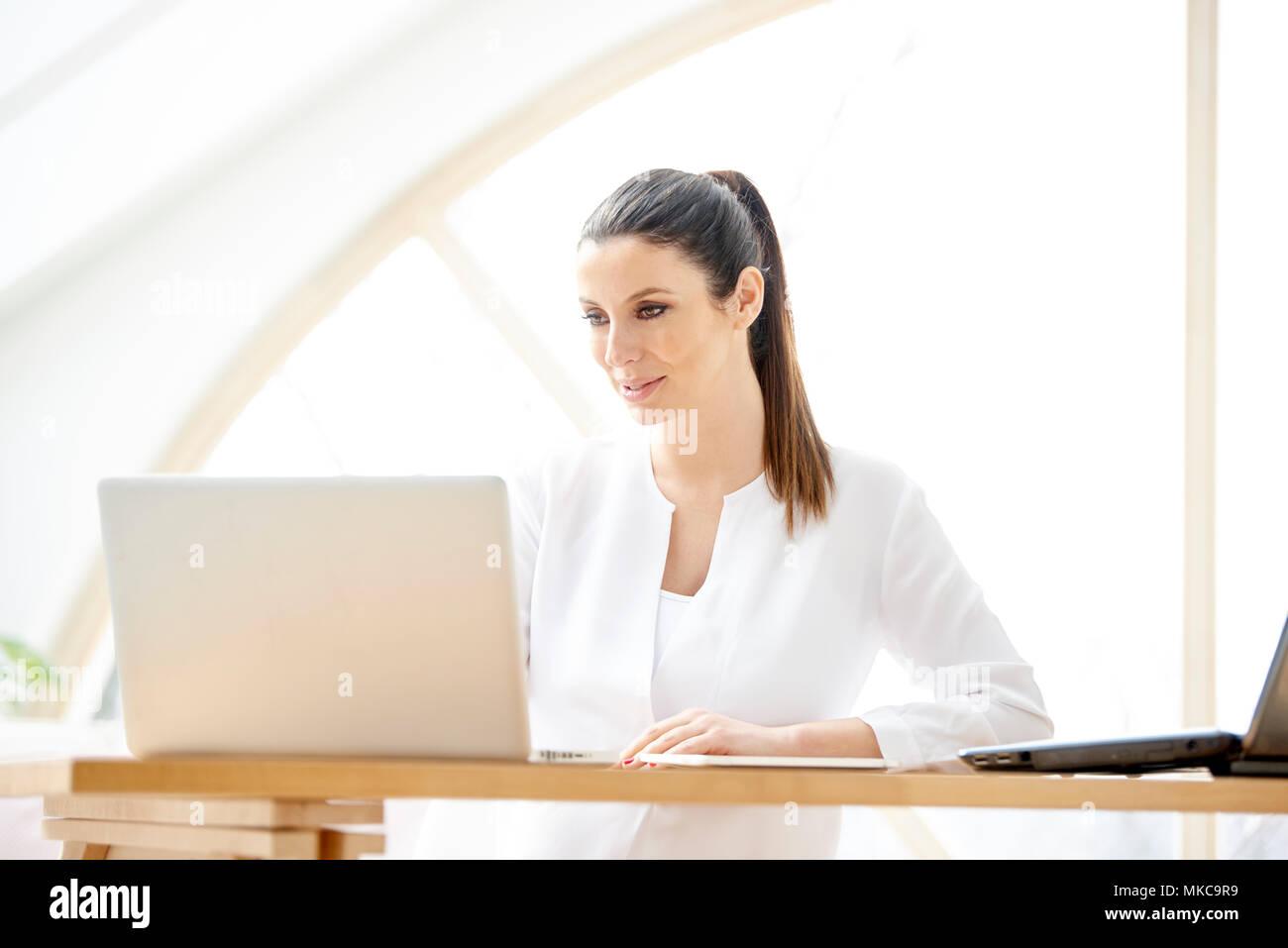 Retrato del joven ayudante de ventas atractiva empresaria utilizando un portátil en la oficina. Imagen De Stock
