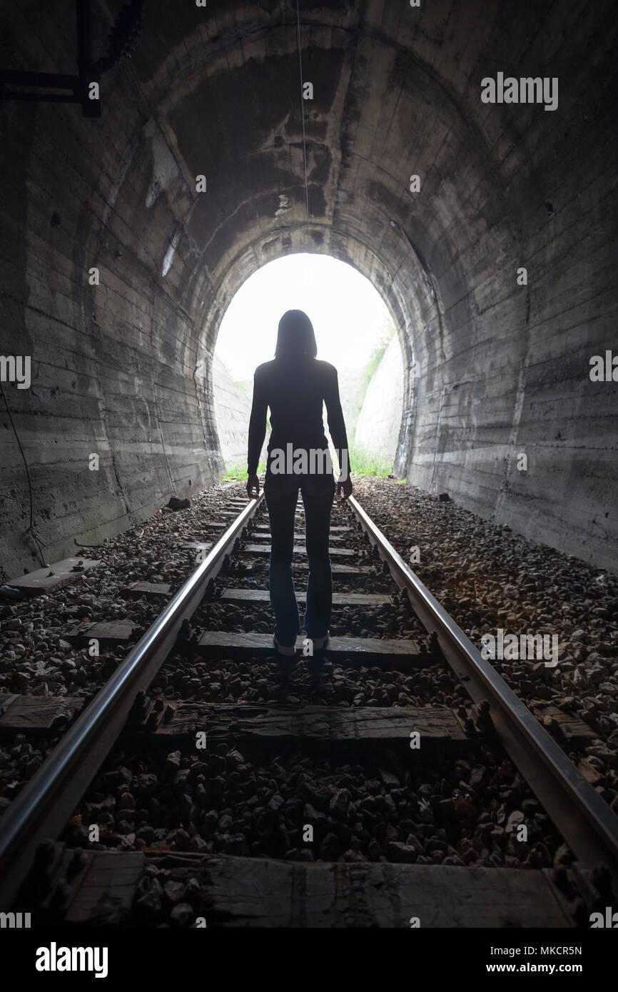 Hombre silueteado en un túnel de pie en el centro de la vía férrea hacia la luz al final del túnel en una imagen conceptual Imagen De Stock