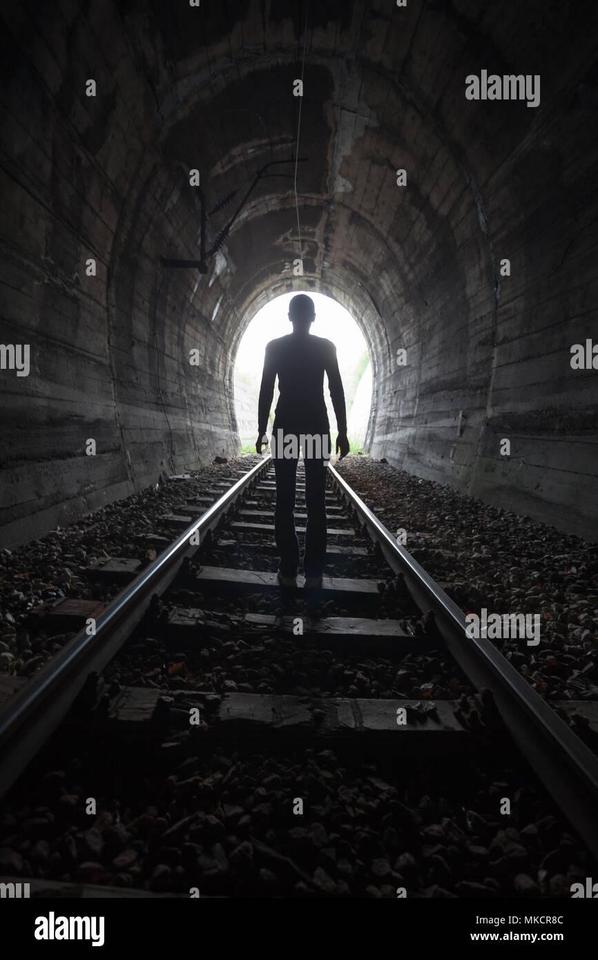 Hombre silueteado en un túnel de pie en el centro de la vía férrea hacia la luz al final del túnel en una imagen conceptual Foto de stock