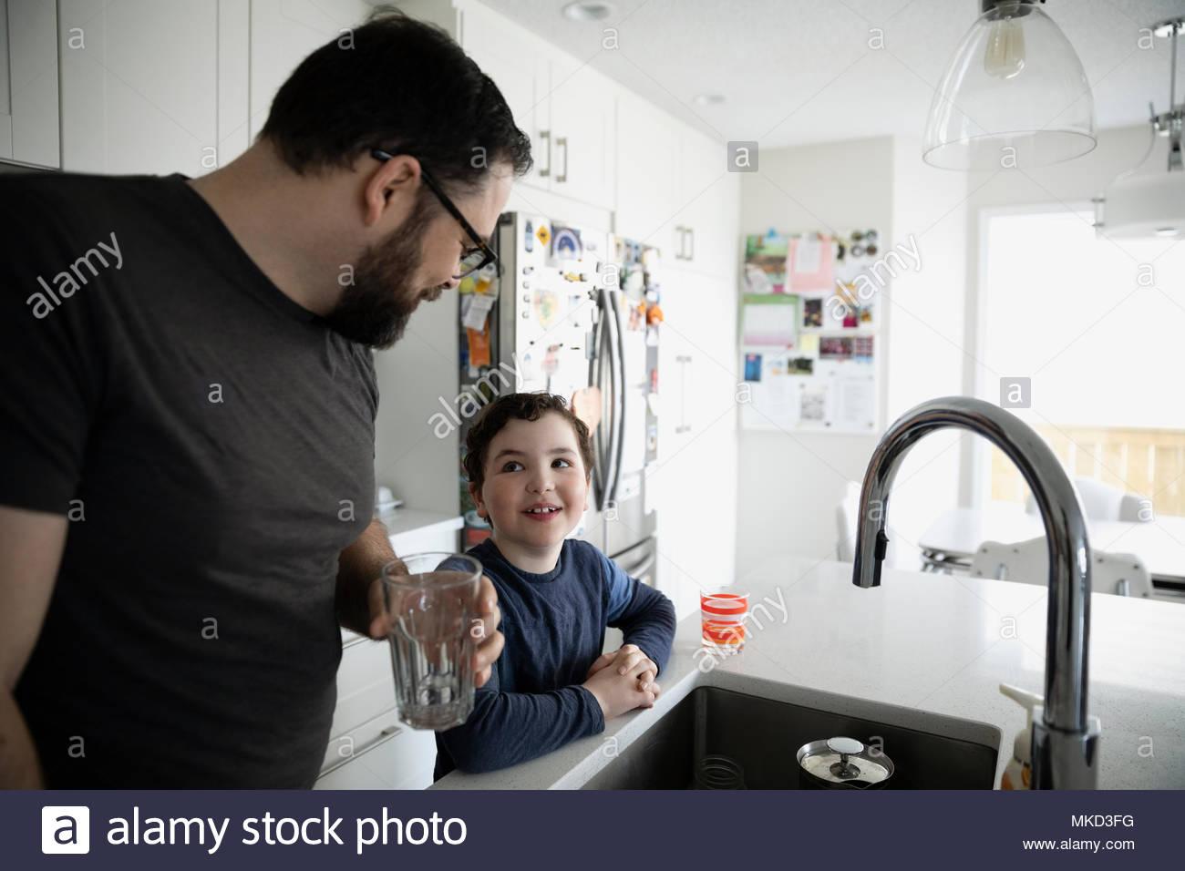 El padre y el hijo, agua potable, hablando al fregadero Imagen De Stock