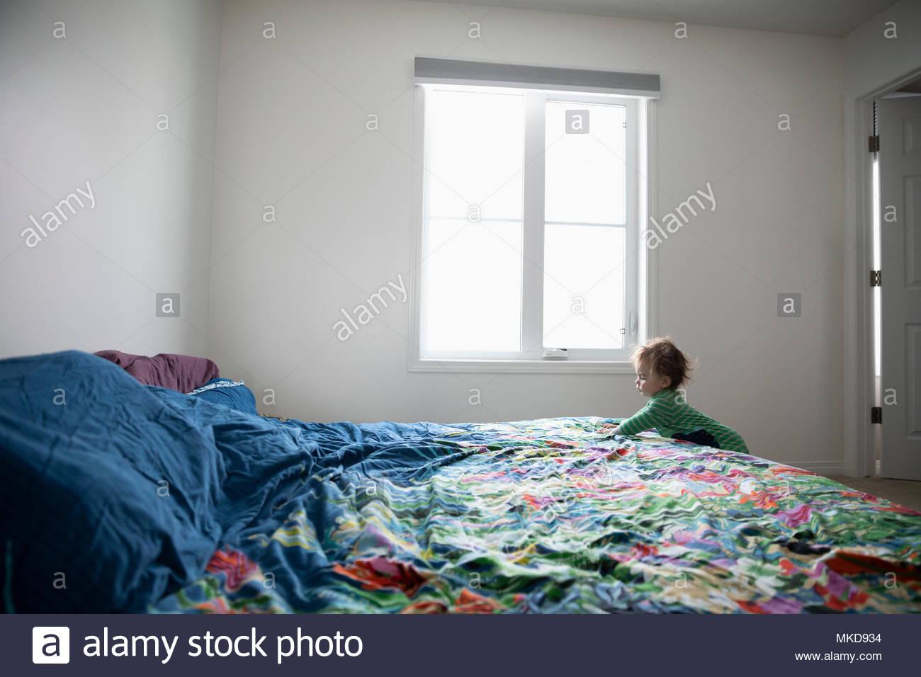 Curioso Baby Boy arrastrándose en la cama Imagen De Stock