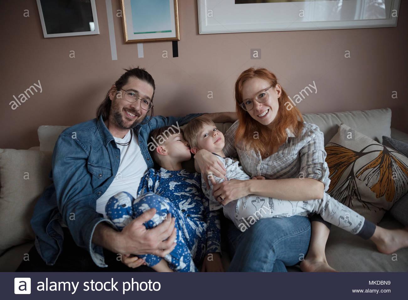 Retrato sonriente, feliz familia en el sofá de la sala Imagen De Stock