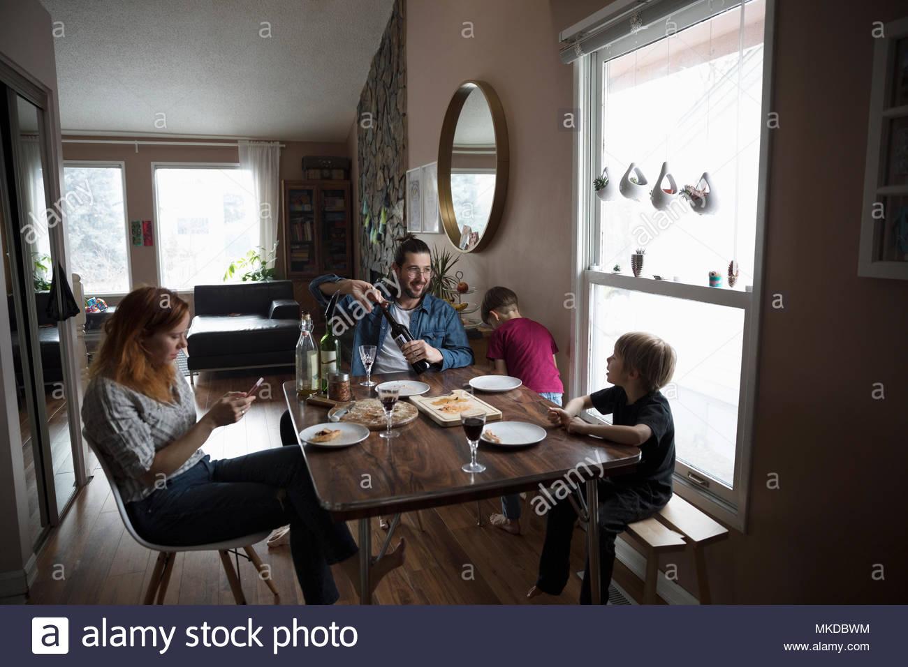 Familia comiendo pizza en la mesa de comedor Imagen De Stock