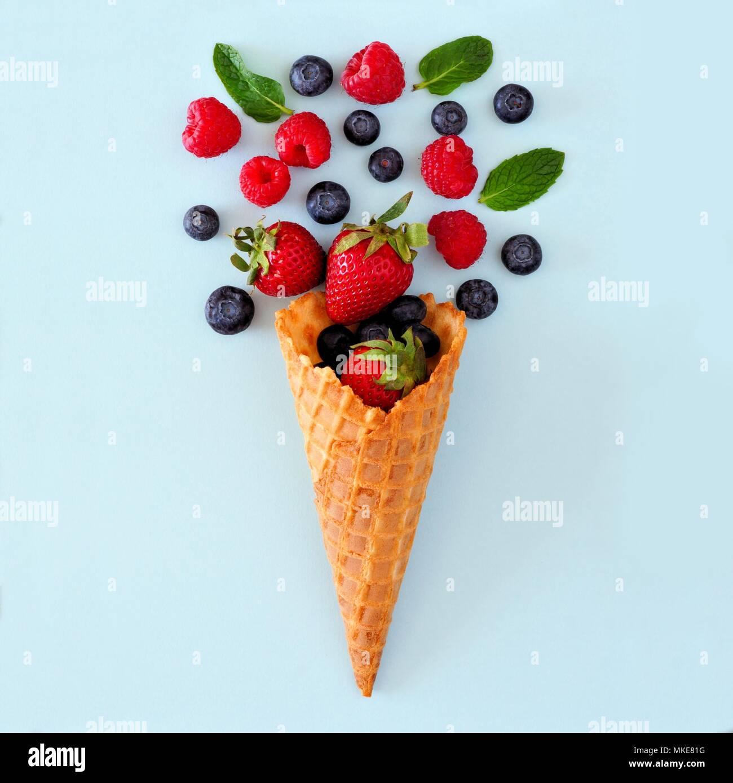 Surtido de frutas de baya en barquillo de helado. Concepto laicos plana sobre un fondo azul pastel. Imagen De Stock