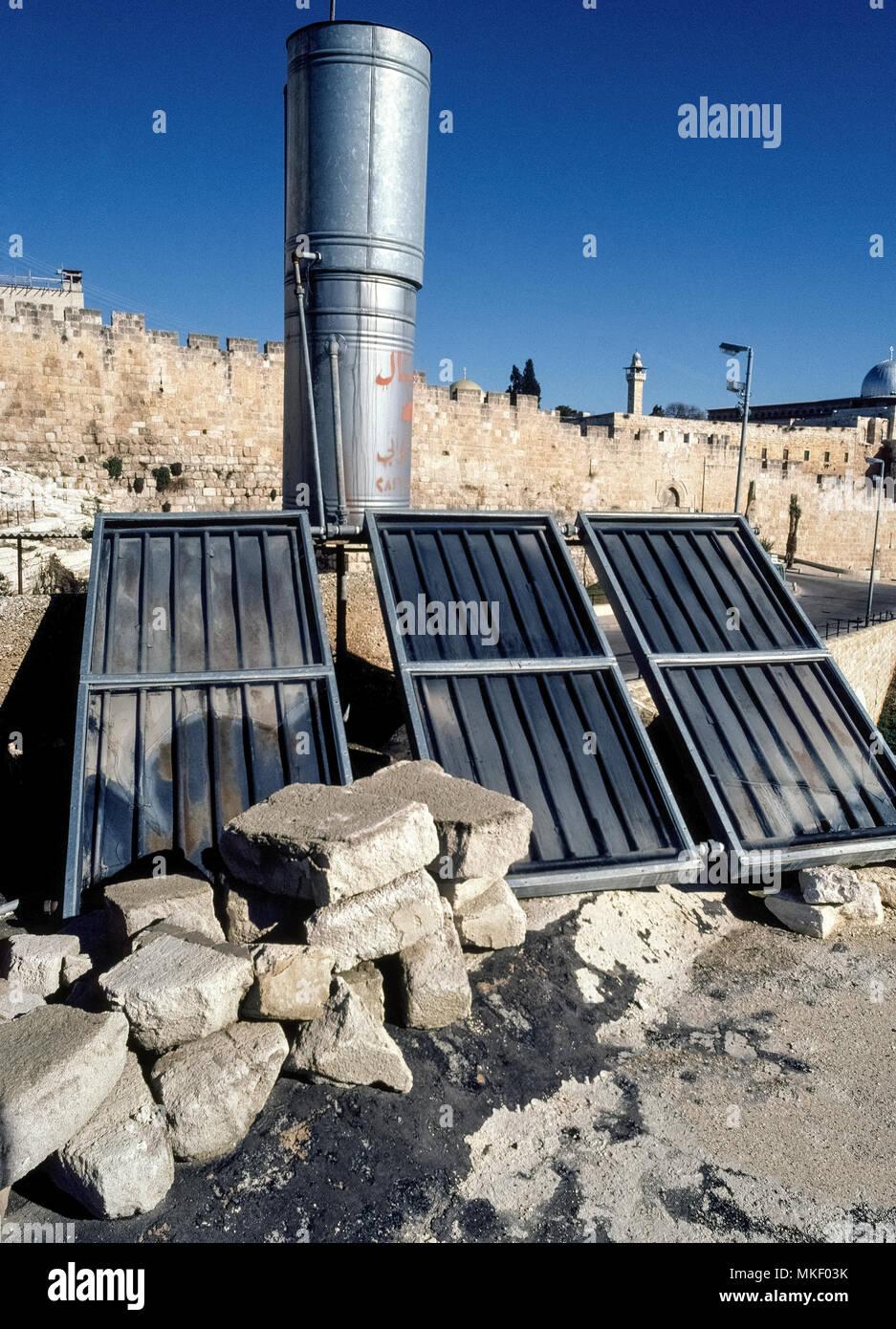 Tres paneles solares de plástico negro acanalada detrás de paneles de vidrio absorben los rayos del sol para crear un simple techo calefactor que proporciona agua caliente a una casa en Jerusalén, la dividida ciudad de Oriente Medio que es reclamada tanto por Israel y Palestina. Estos pequeños dispositivos térmicos fueron desarrollados comercialmente en Israel en 1950, y hoy en día la energía solar calentadores de agua se encuentran en casi el 90 por ciento de todos los hogares de Israel. Imagen De Stock