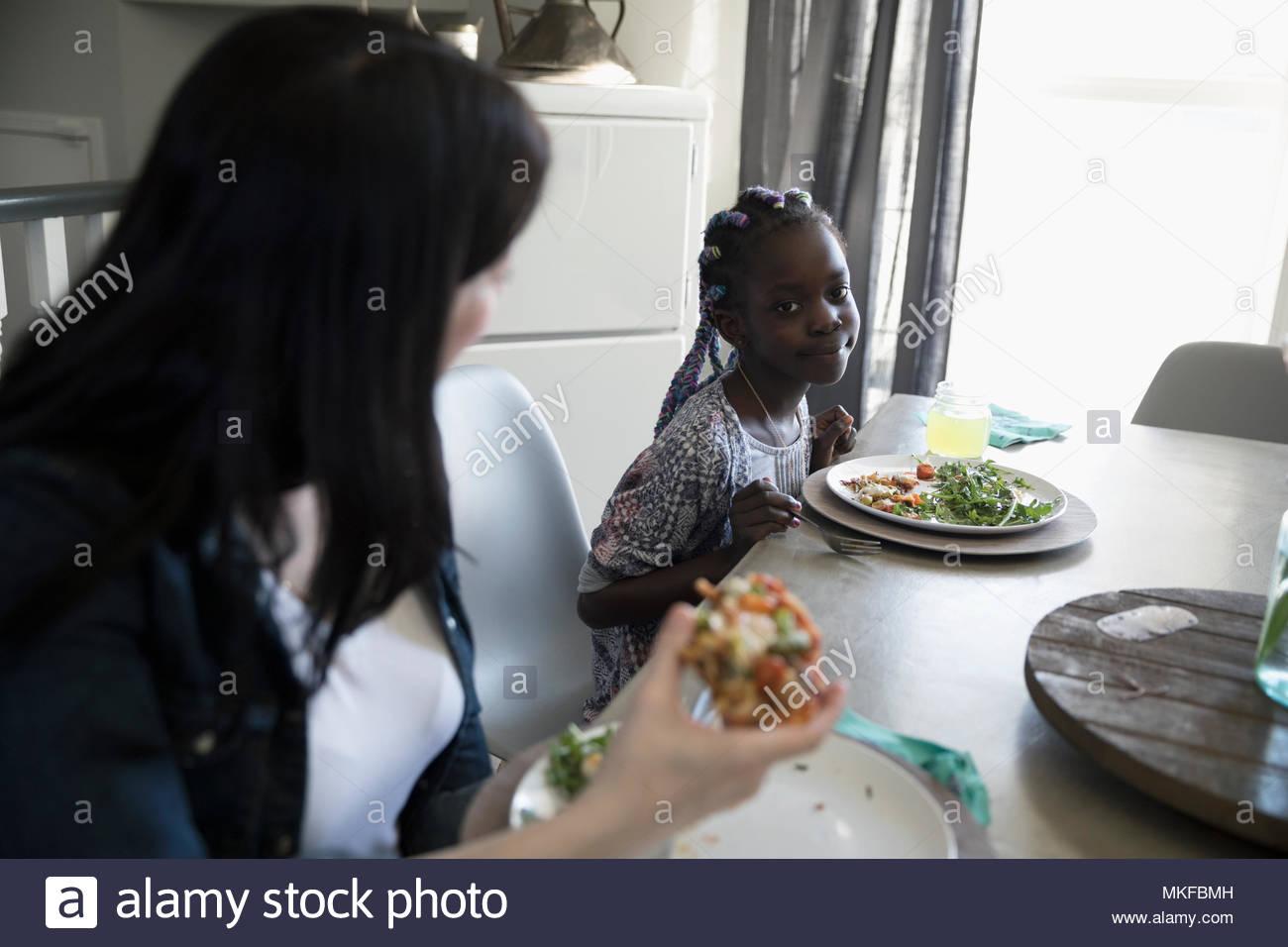 Madre e hija comer pizza y ensaladas en la mesa de comedor Imagen De Stock