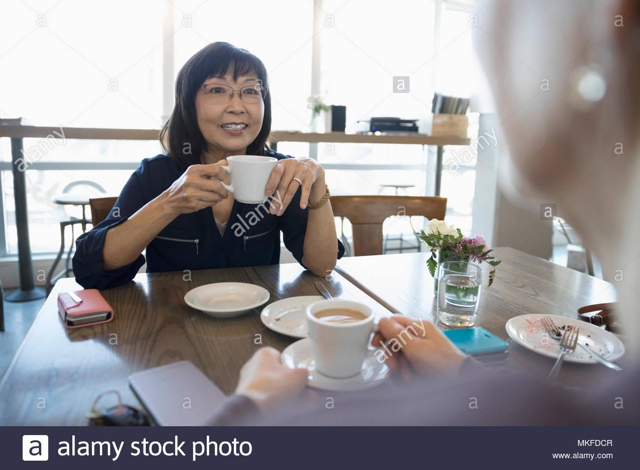 Las mujeres ancianas activas amigos tomando café y hablando en el cafe Imagen De Stock