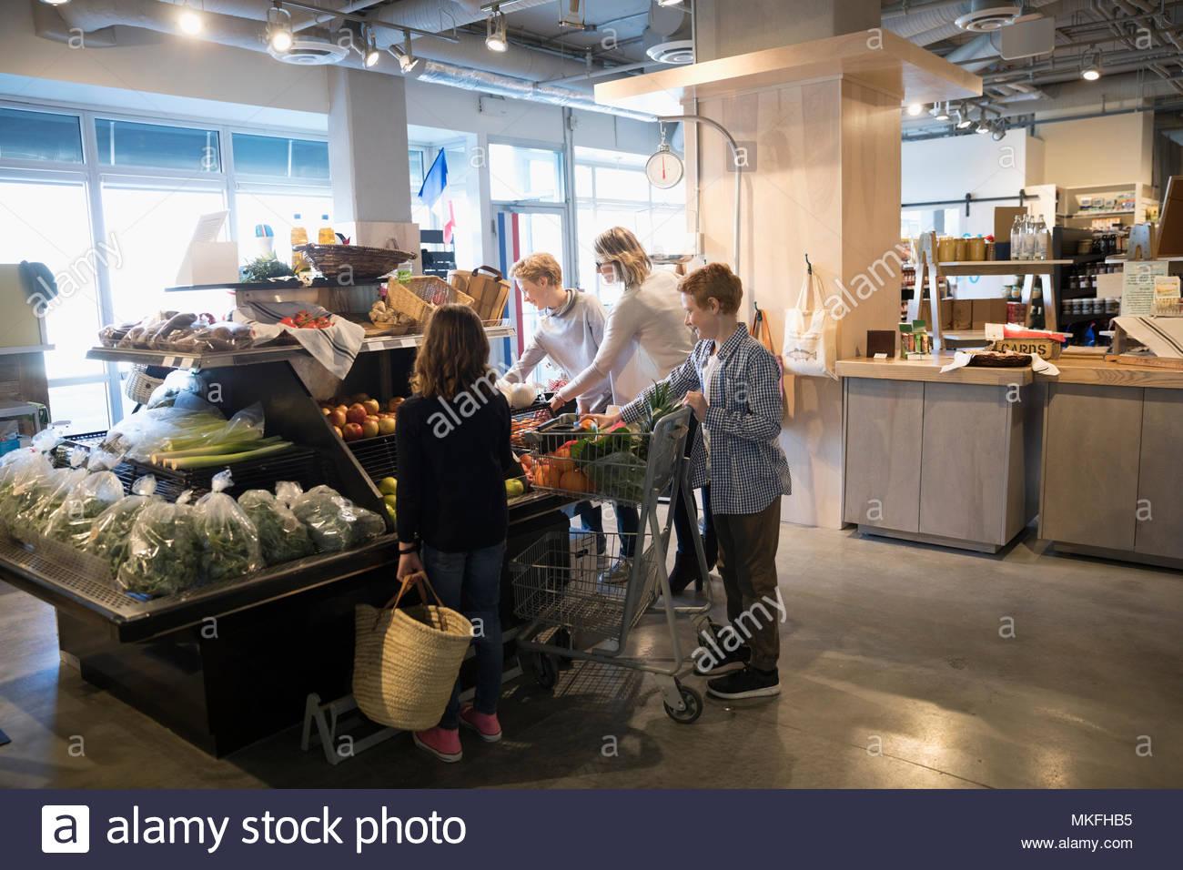 Compras de comestibles de la familia, eligiendo producir en el mercado Imagen De Stock
