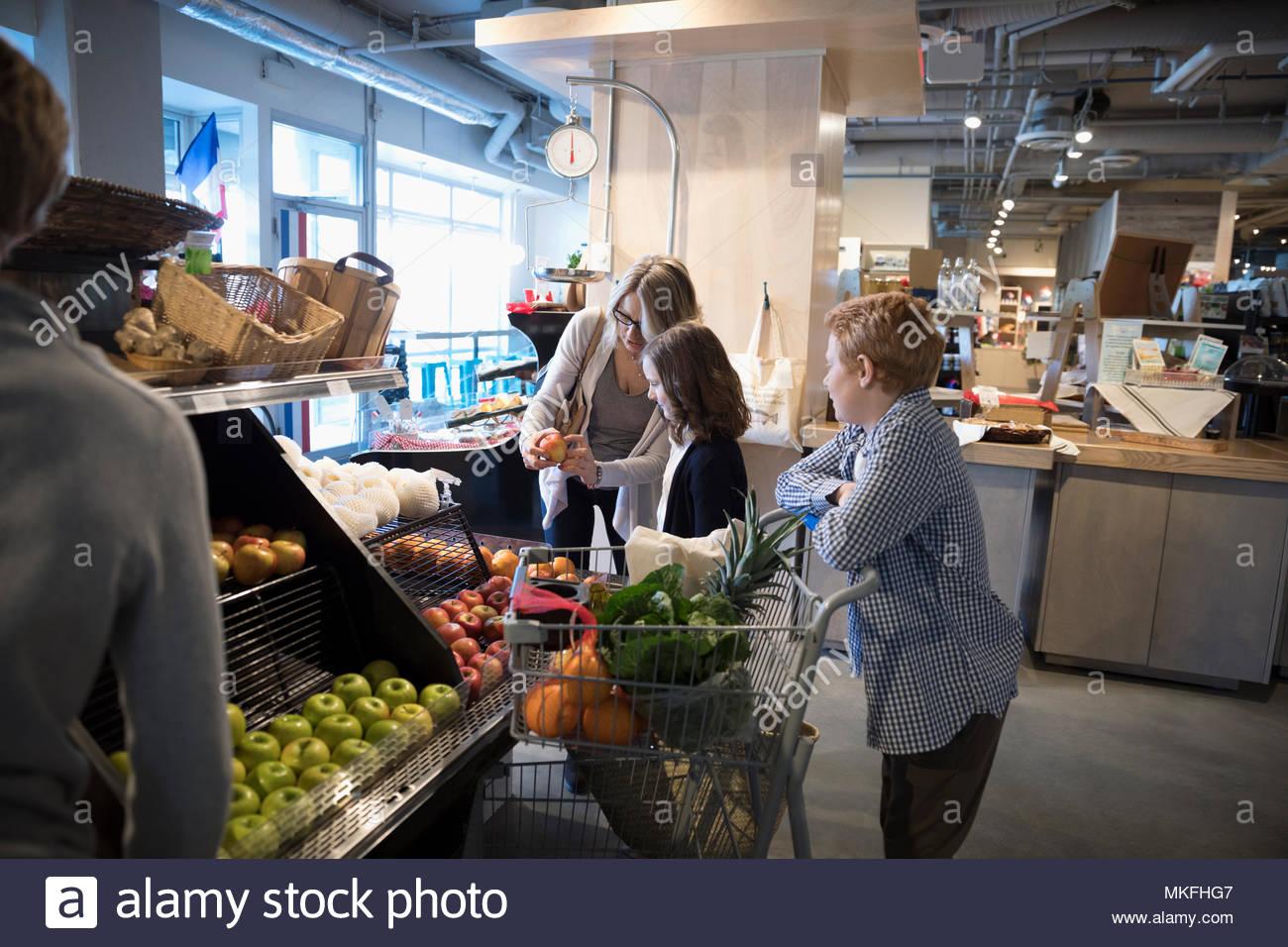 La madre y los hijos compras de supermercado, sacando las manzanas en el mercado Imagen De Stock
