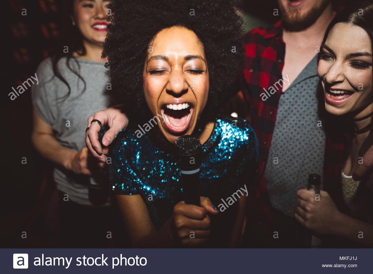 Exuberante mujer joven milenaria cantar karaoke Imagen De Stock