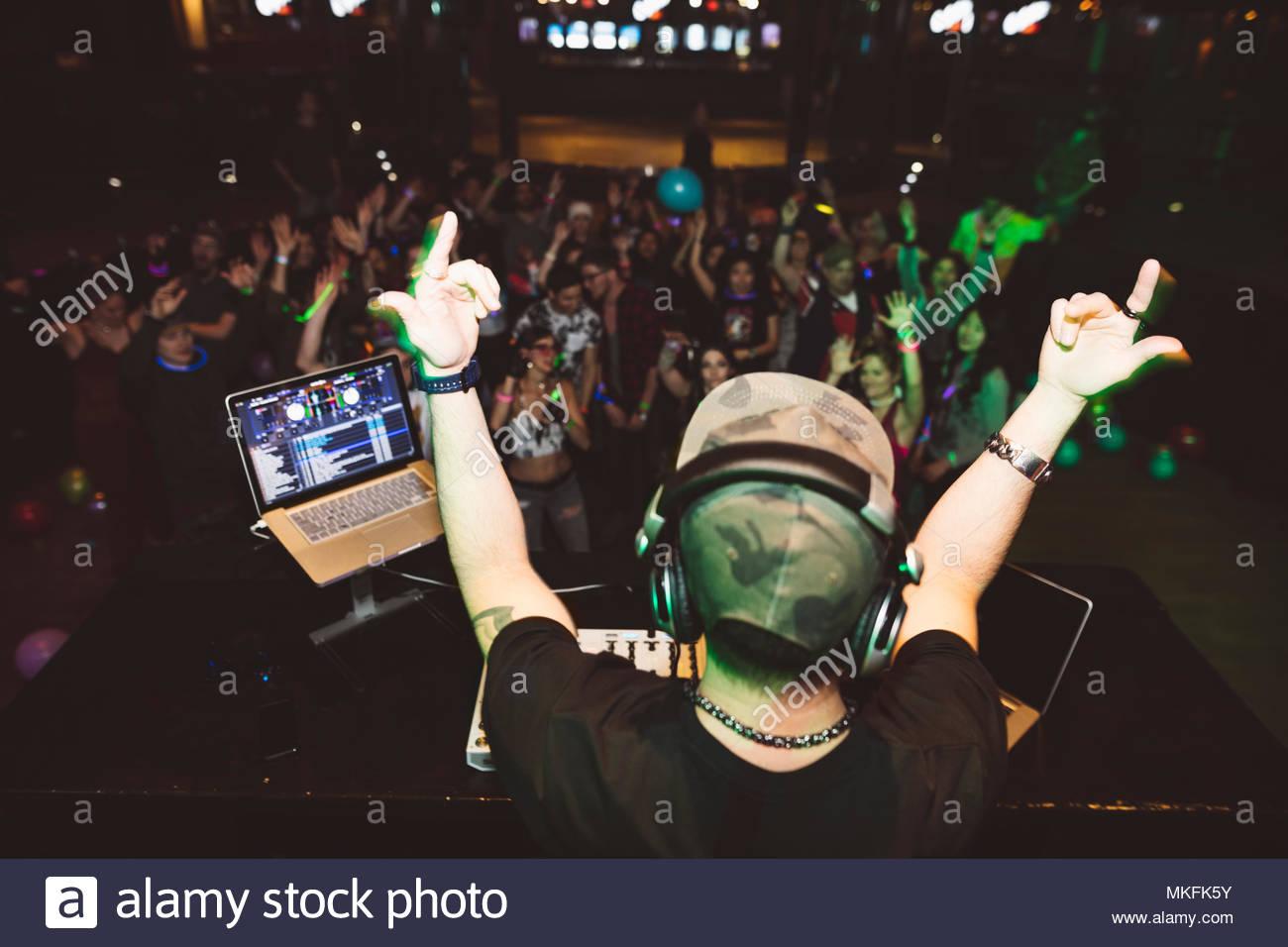 DJ entusiasta sobre el escenario gesticulando a multitud en discoteca Imagen De Stock
