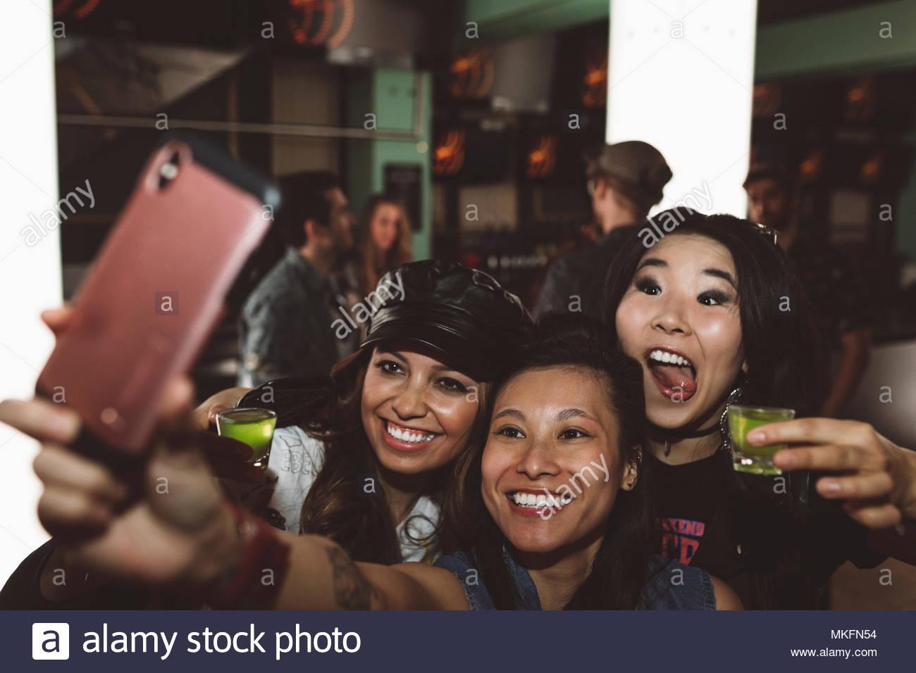 Juguetón, exuberantes hembras jóvenes amigos milenario tomando fotos y tomando selfie en discoteca Imagen De Stock