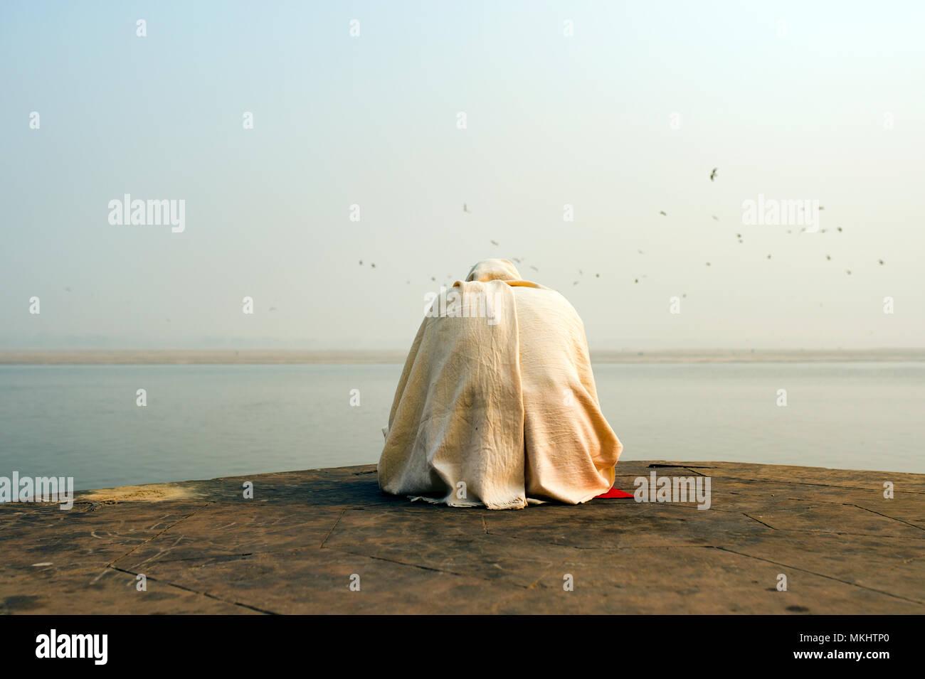 Un hombre vestido de blanco santo rezando y meditando en uno de los numerosos Ghats de Varanasi en frente del río sagrado Ganges, India. Foto de stock