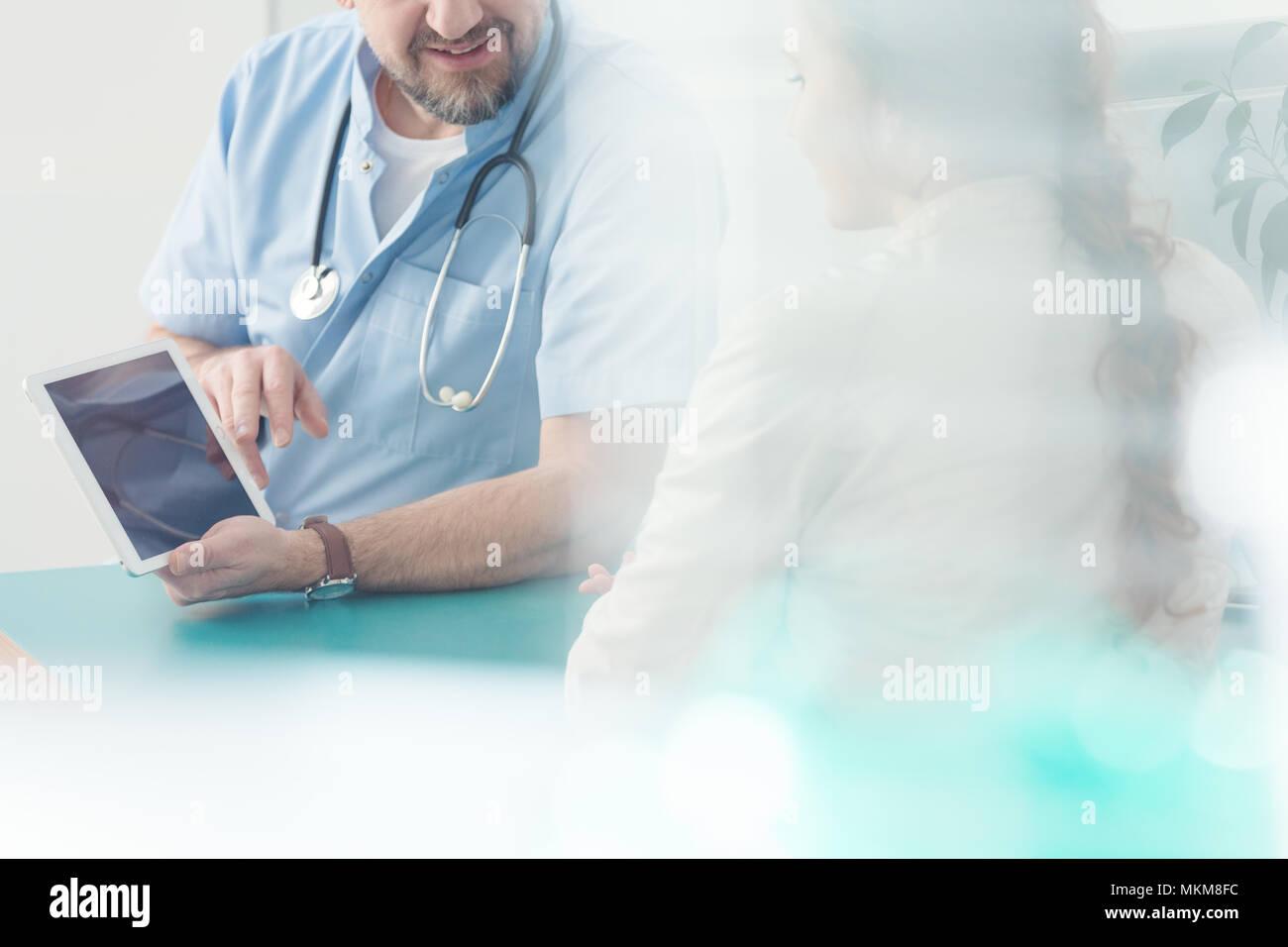 En el cirujano de fondo que muestra información sobre un tablet durante la consulta con una chica Foto de stock
