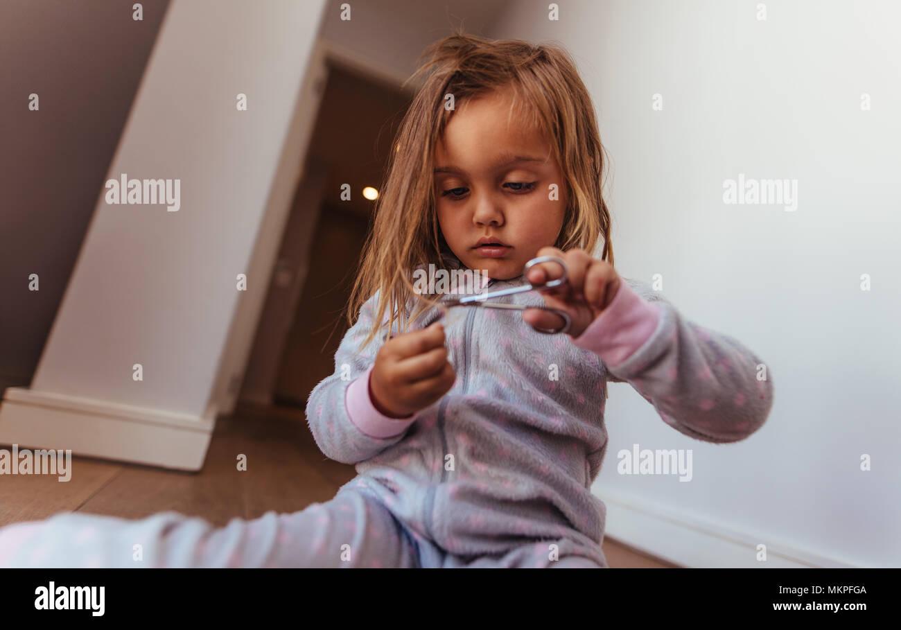 Niña inocente ella cortando el pelo con unas tijeras. Niña recortar su propio cabello con tijeras en casa. Imagen De Stock