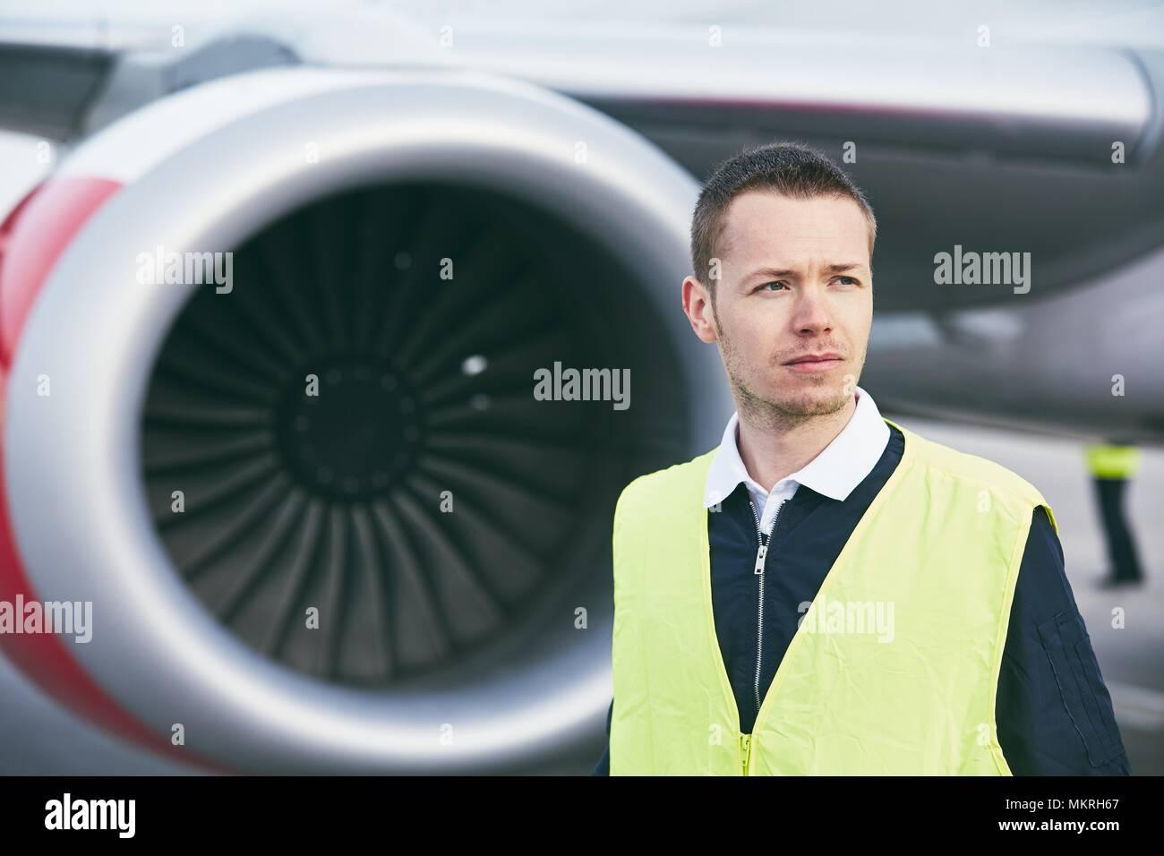 Miembro trabajador de la tripulación en tierra en el aeropuerto comprobando antes de vuelo del avión. Imagen De Stock
