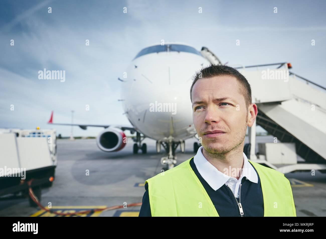 Miembro trabajador de la tripulación en tierra en el aeropuerto en la parte delantera del avión. Imagen De Stock
