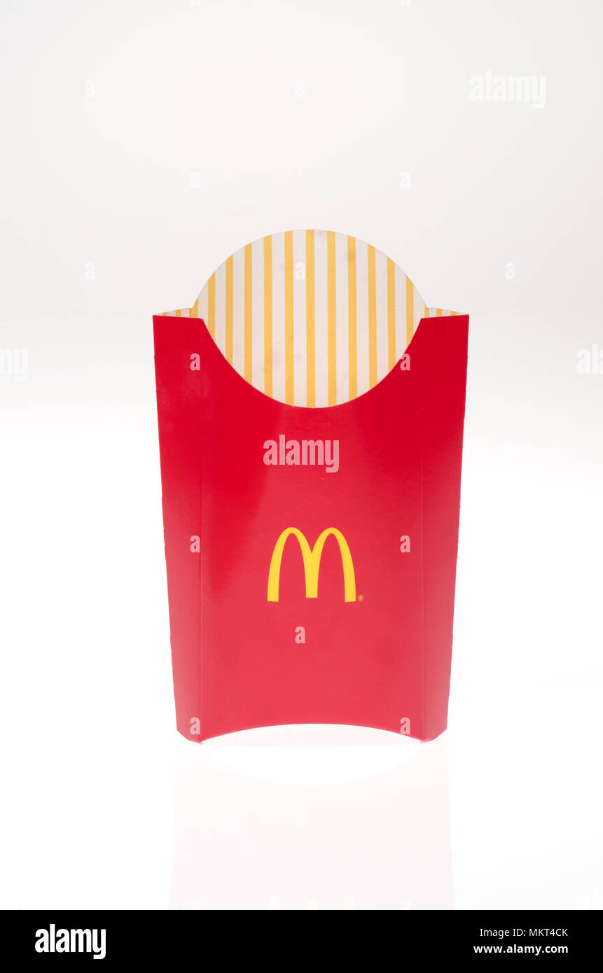 Vaciar las patatas fritas de Mcdonald's contenedor sobre fondo blanco. Imagen De Stock