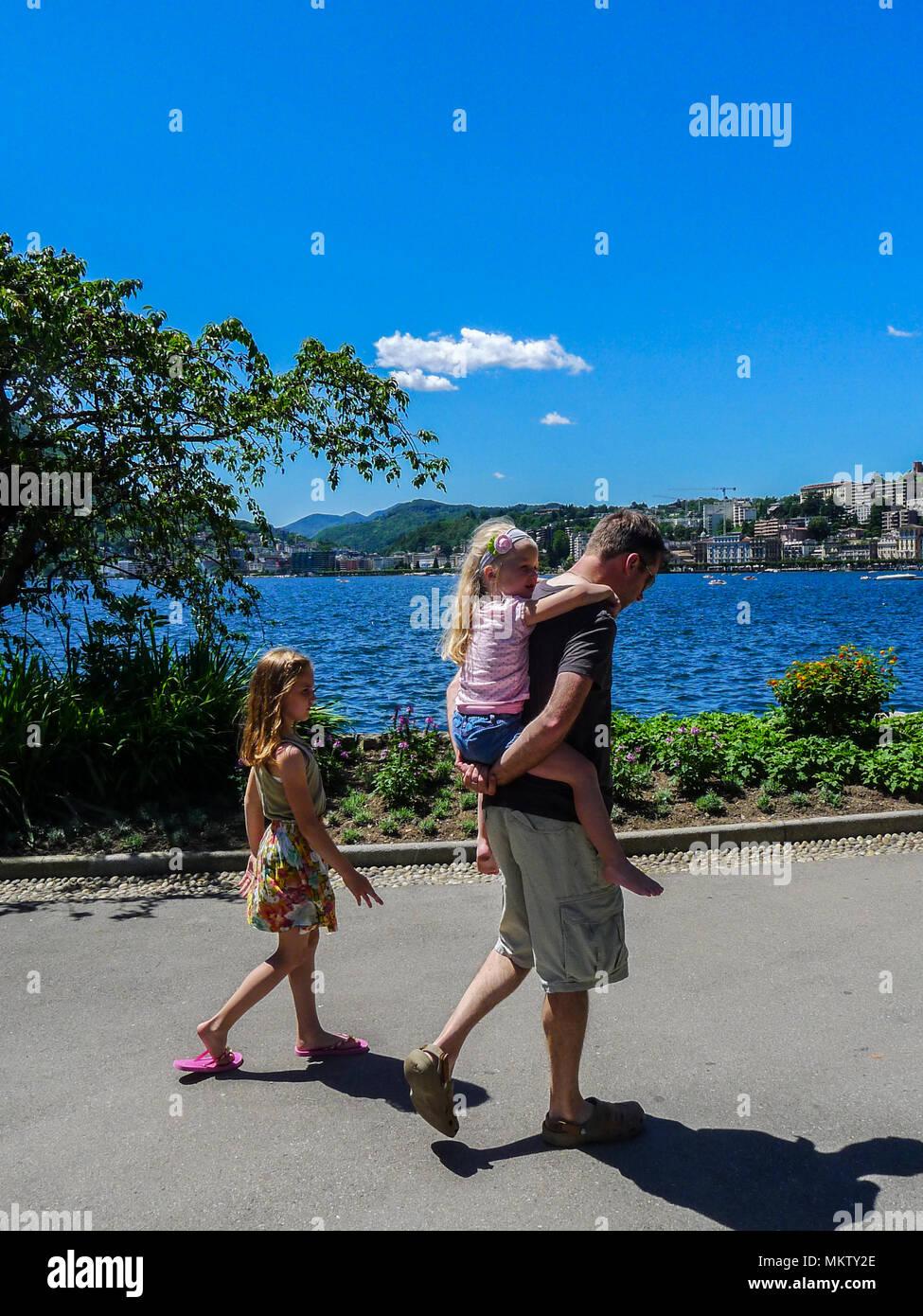 Padre hija papá niño niña kid piggyback piggy back soleados días de verano, la vida familiar de Lugano (Suiza) el día del padre concepto agregativas de conexión Imagen De Stock