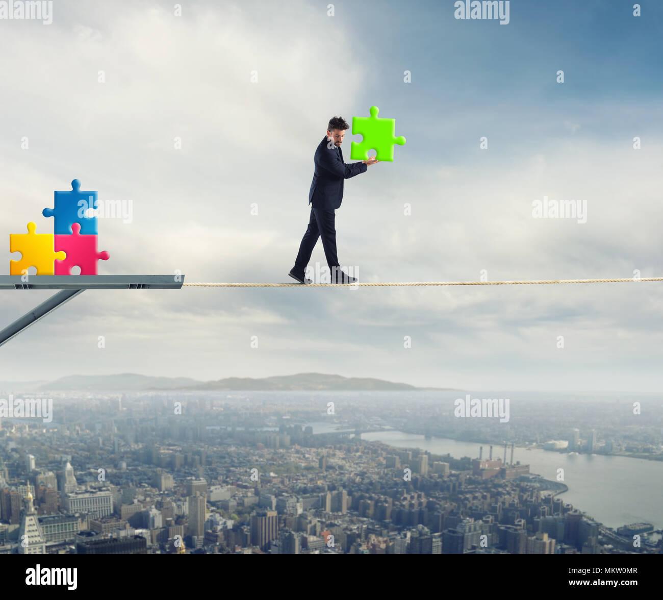 El empresario lleva una pieza del puzzle mientras él caminando sobre una cuerda. concepto de pieza faltante Foto de stock