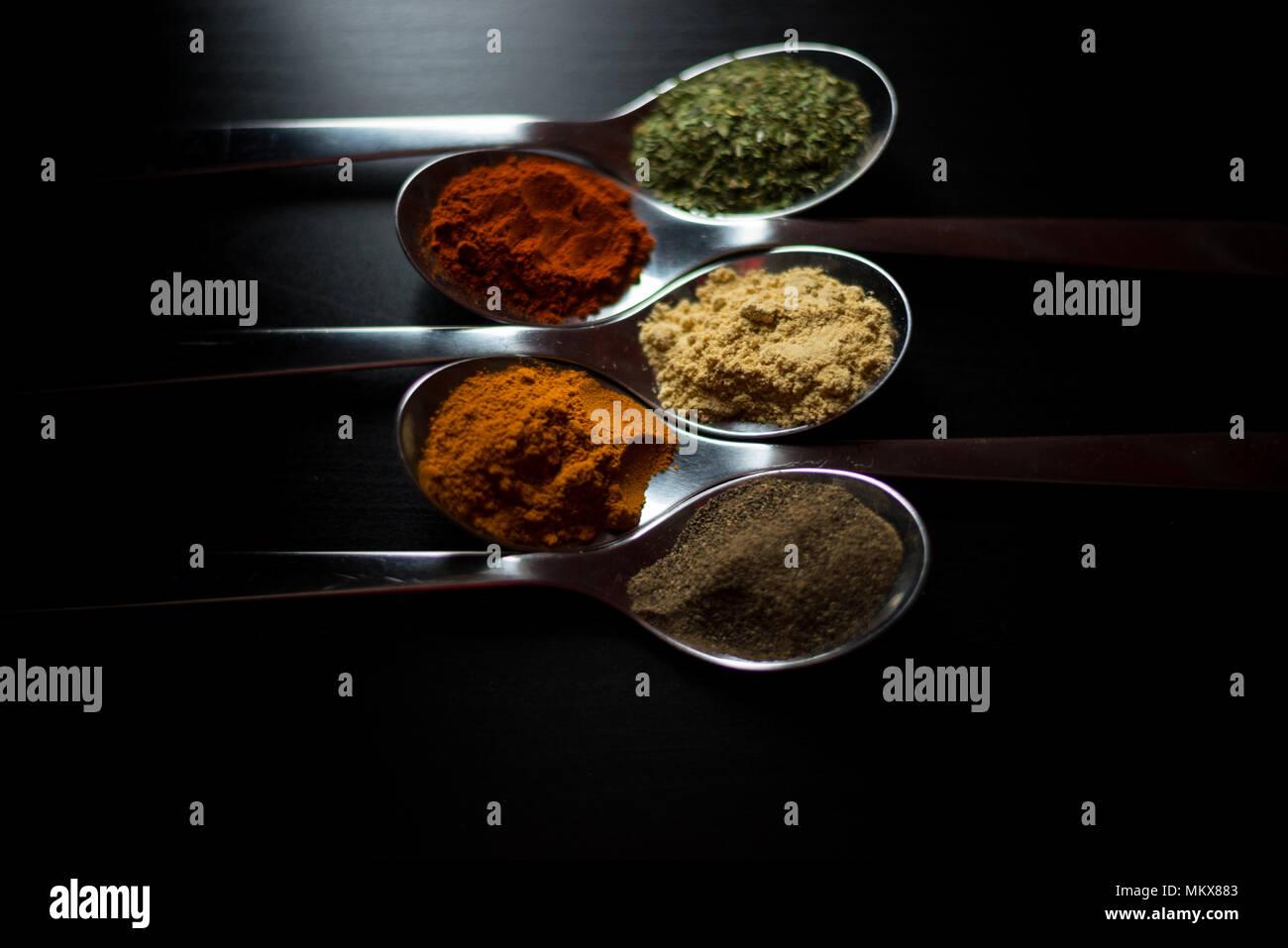 Especias coloreadas en cucharas de plata, colocados sobre una mesa de madera negra. Pimienta, pimienta, sal, albahaca, mostaza Foto de stock