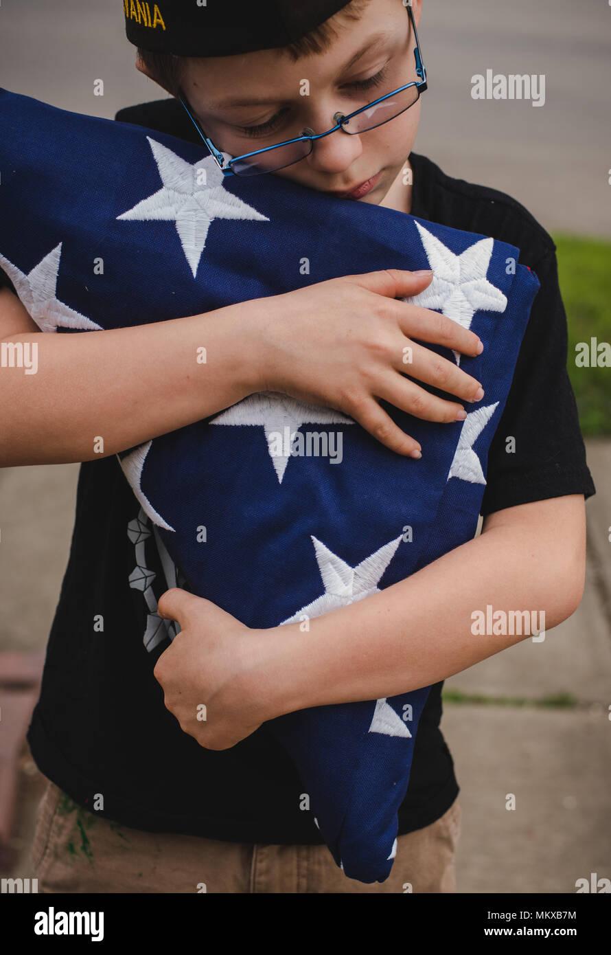 Un joven niño sosteniendo una bandera plegada. Imagen De Stock