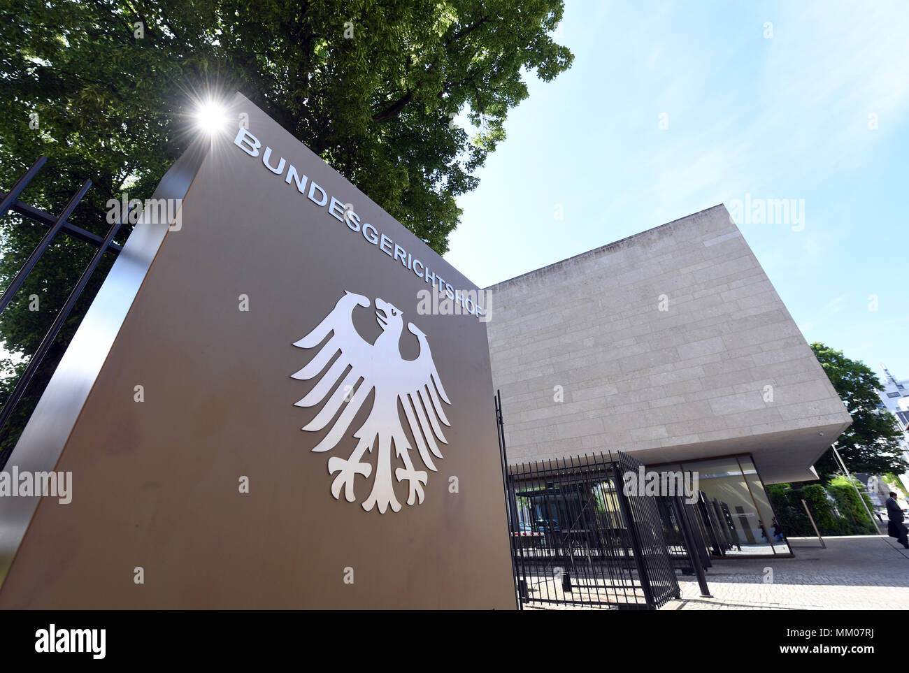 09 de mayo de 2018, Alemania, Karlsruhe: un cartel con el águila alemana y la rotulación del Supremo Tribunal Federal. El Tribunal Supremo Federal está negociando si la música plataforma Youtube lleva la responsabilidad por las violaciones de los derechos de autor de sus usuarios. Un productor de música ha venido demandando a la filial de Google durante diez años. Foto: Uli Deck/dpa Foto de stock