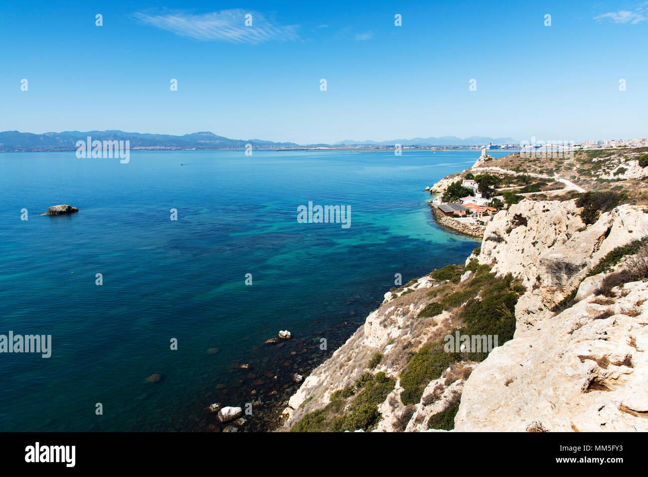 Una vista de la costa de Sant Elia en Cagliari, Cerdeña, destacando el Prezzemolo torre a la derecha y el puerto de Cagliari, en el fondo Imagen De Stock