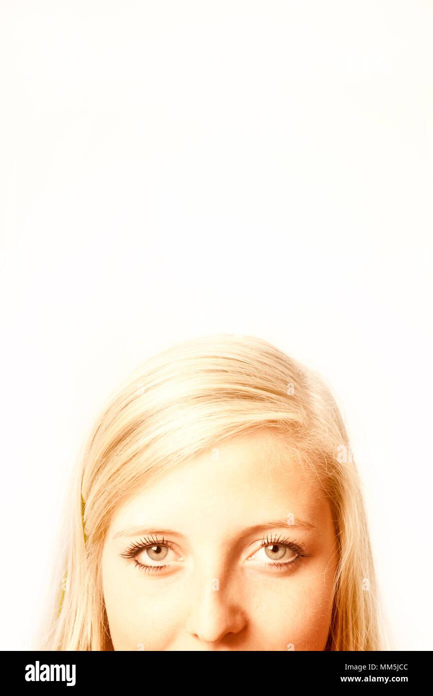La mitad superior de la cara de una joven mujer rubia, sólo los ojos visibles y copia espacio encima Imagen De Stock
