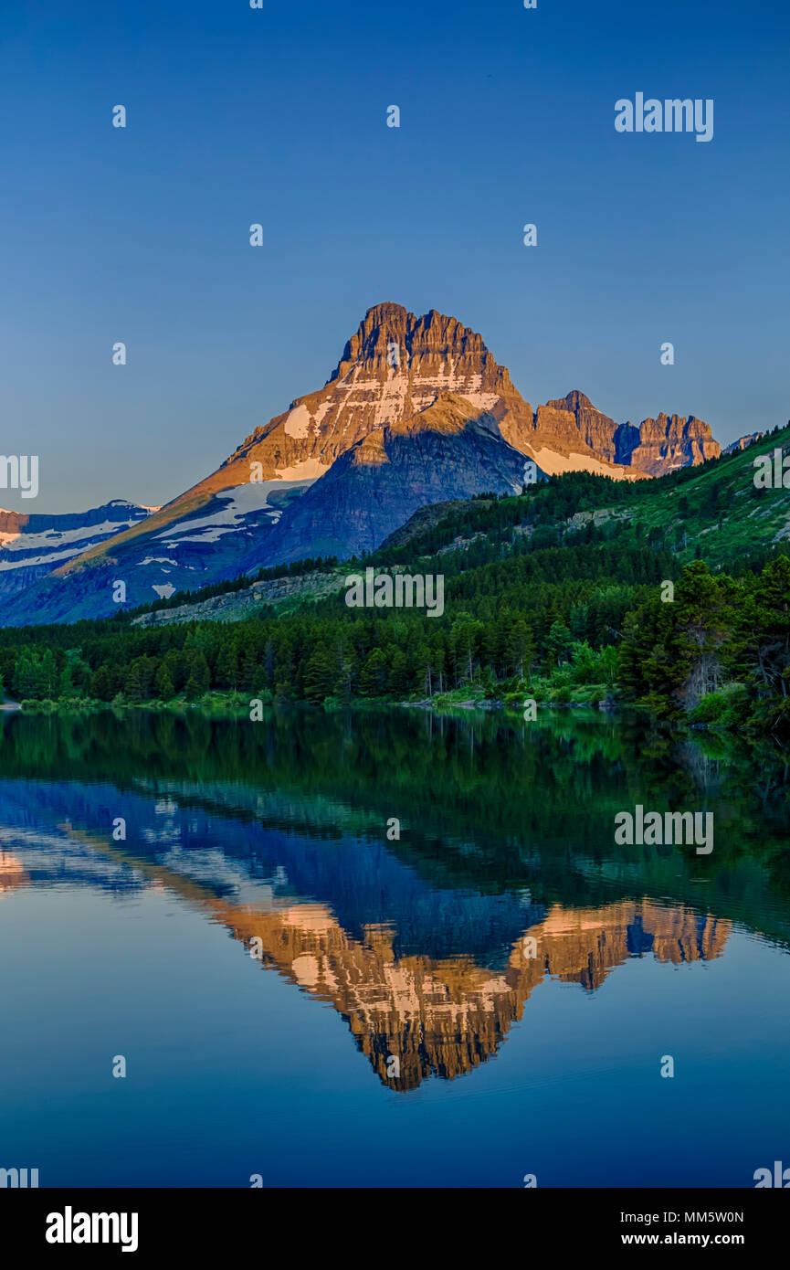 Monte Wilbur se refleja en el lago Swiftcurrent al amanecer en el parque nacional de Glacier, Montana, EE.UU. Imagen De Stock