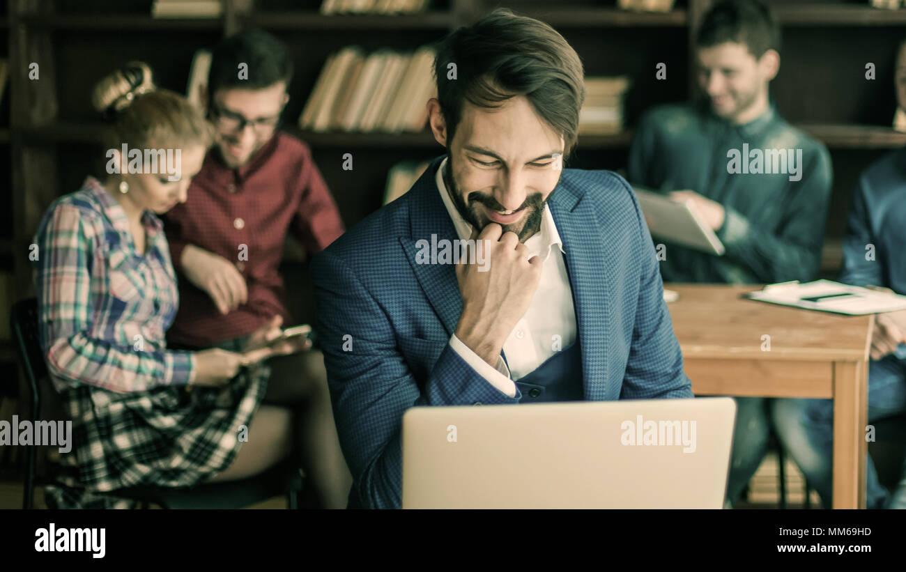 Gerente de ventas con ordenador portátil en el fondo del equipo empresarial en Foto de stock