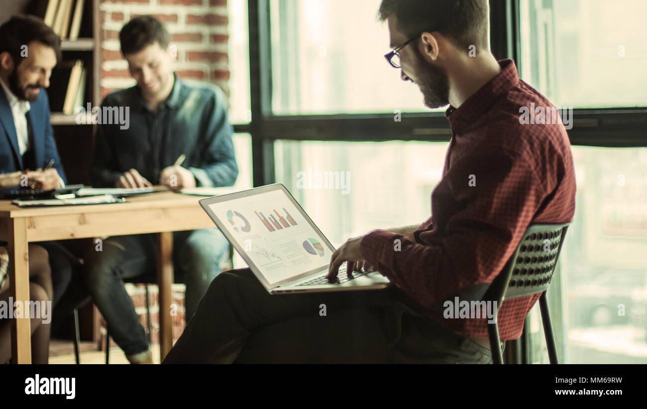 El Director comercial de trabajar con gráficos financieros en el portátil. Imagen De Stock