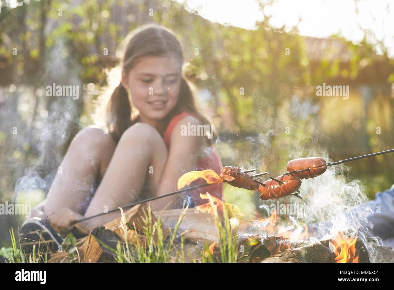 Los niños disfrutan de CAMPFIRE. Chica salchichas tostado en el jardín. Imagen De Stock