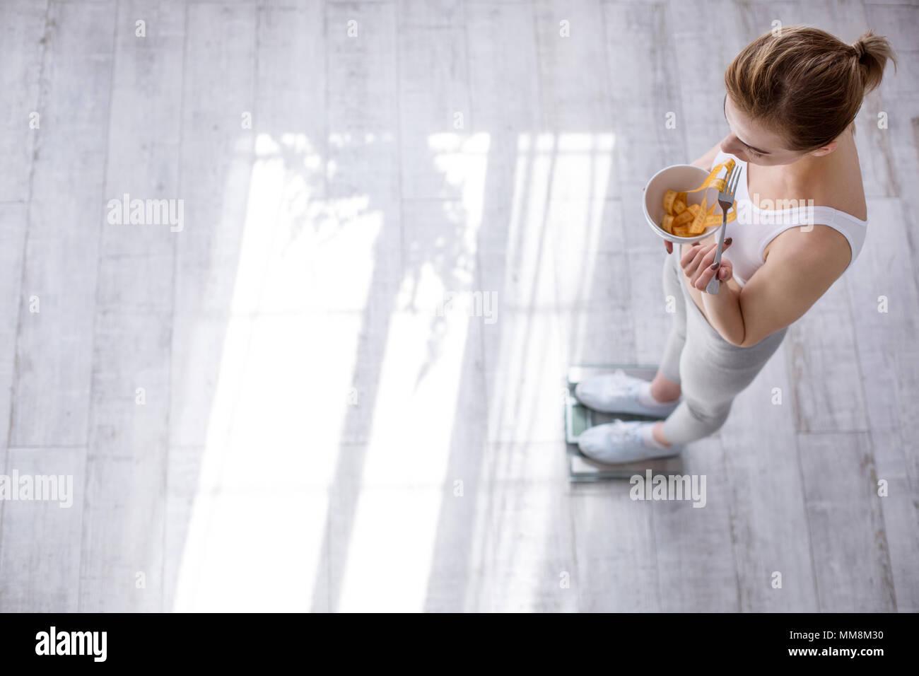 Bonito joven mujer sosteniendo un cuenco con cinta centímetro Imagen De Stock