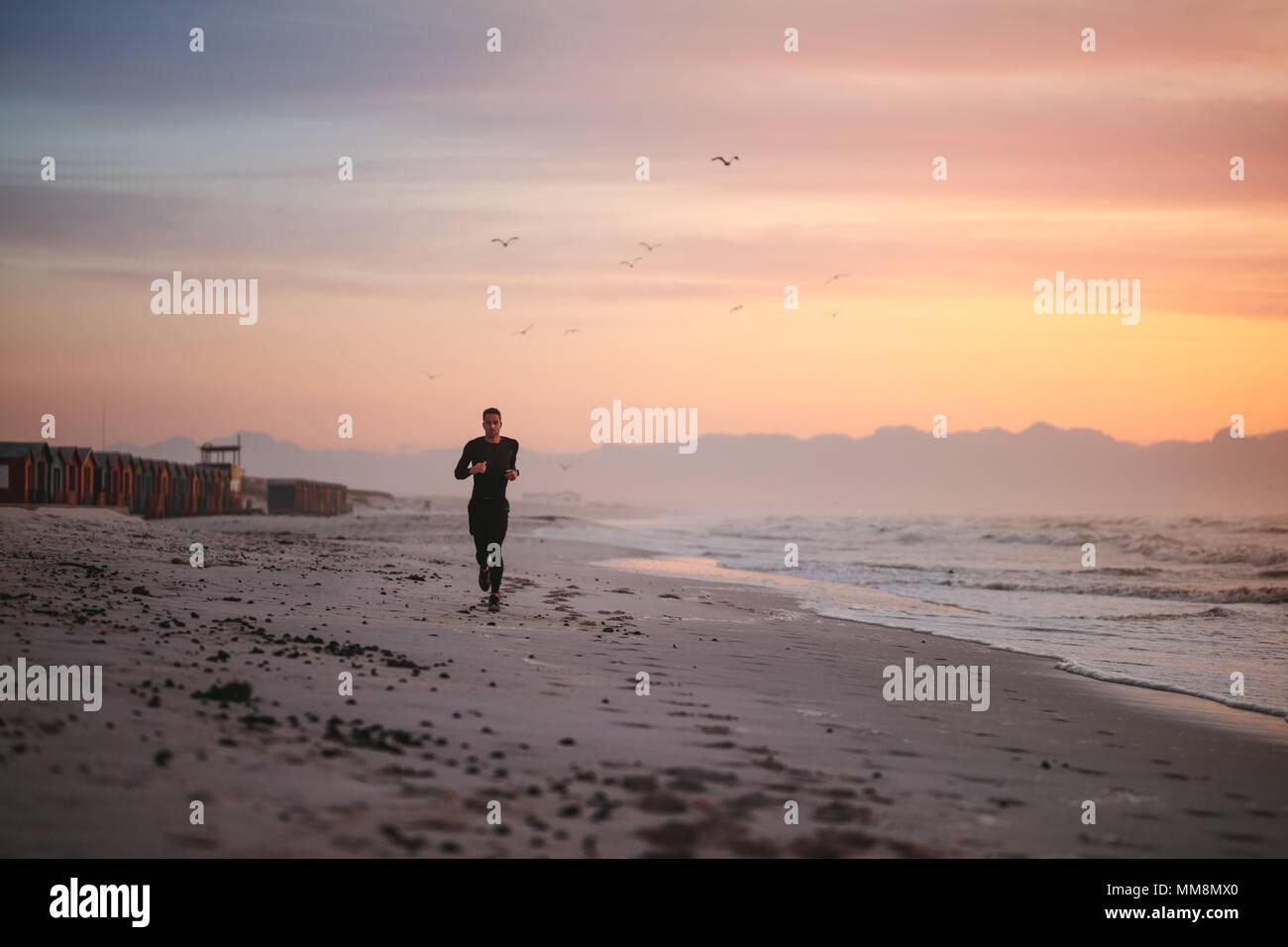 Disparo de longitud completa de colocar hombres runner corriendo en la playa por la mañana. Fitness hombre footing en la orilla del mar. Imagen De Stock