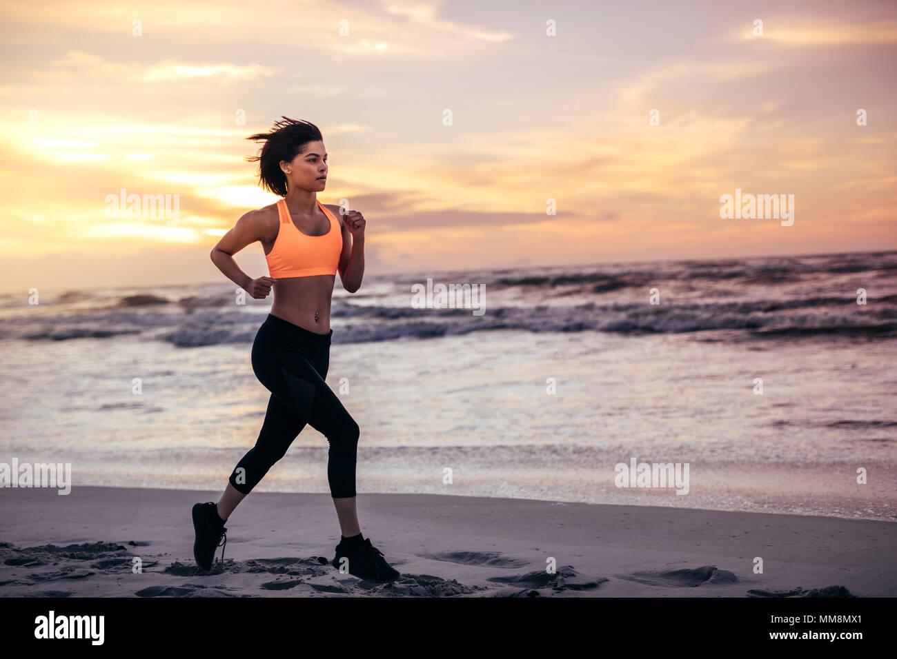 Deportista que corre a lo largo de la playa por la mañana. Mujer en marcha outfit esprinta en la orilla del mar. Imagen De Stock