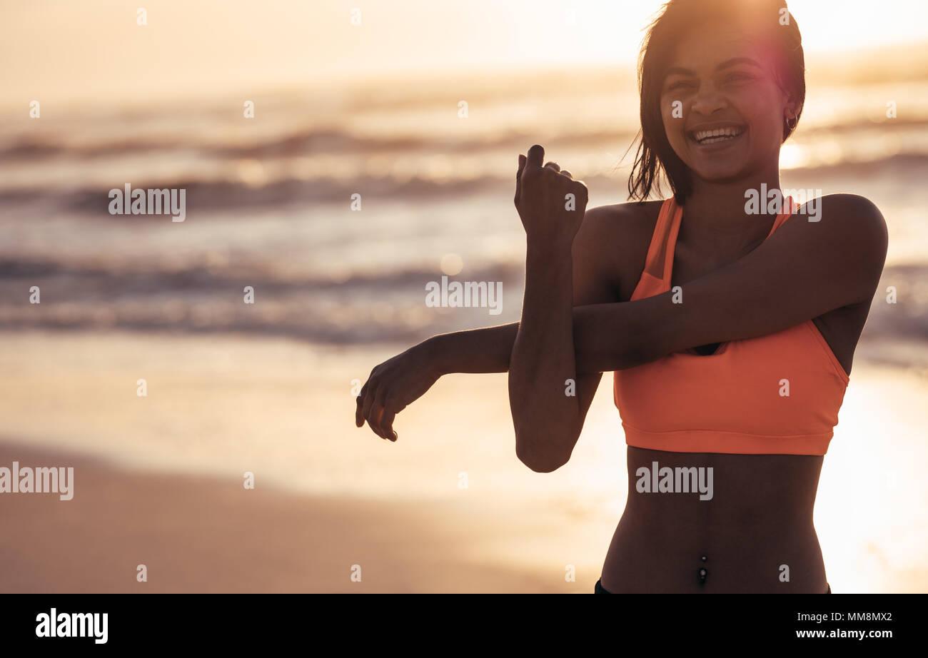 Mujer sonriente estirando los brazos a la orilla del mar. Atleta Femenina haciendo ejercicios de calentamiento en la playa. Imagen De Stock