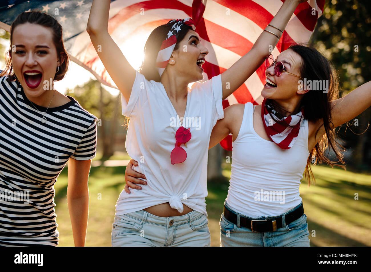 Tres jóvenes amigas con bandera americana se divierten en el parque. Grupo de sonrientes mujeres celebrando el 4 de julio al aire libre. Imagen De Stock