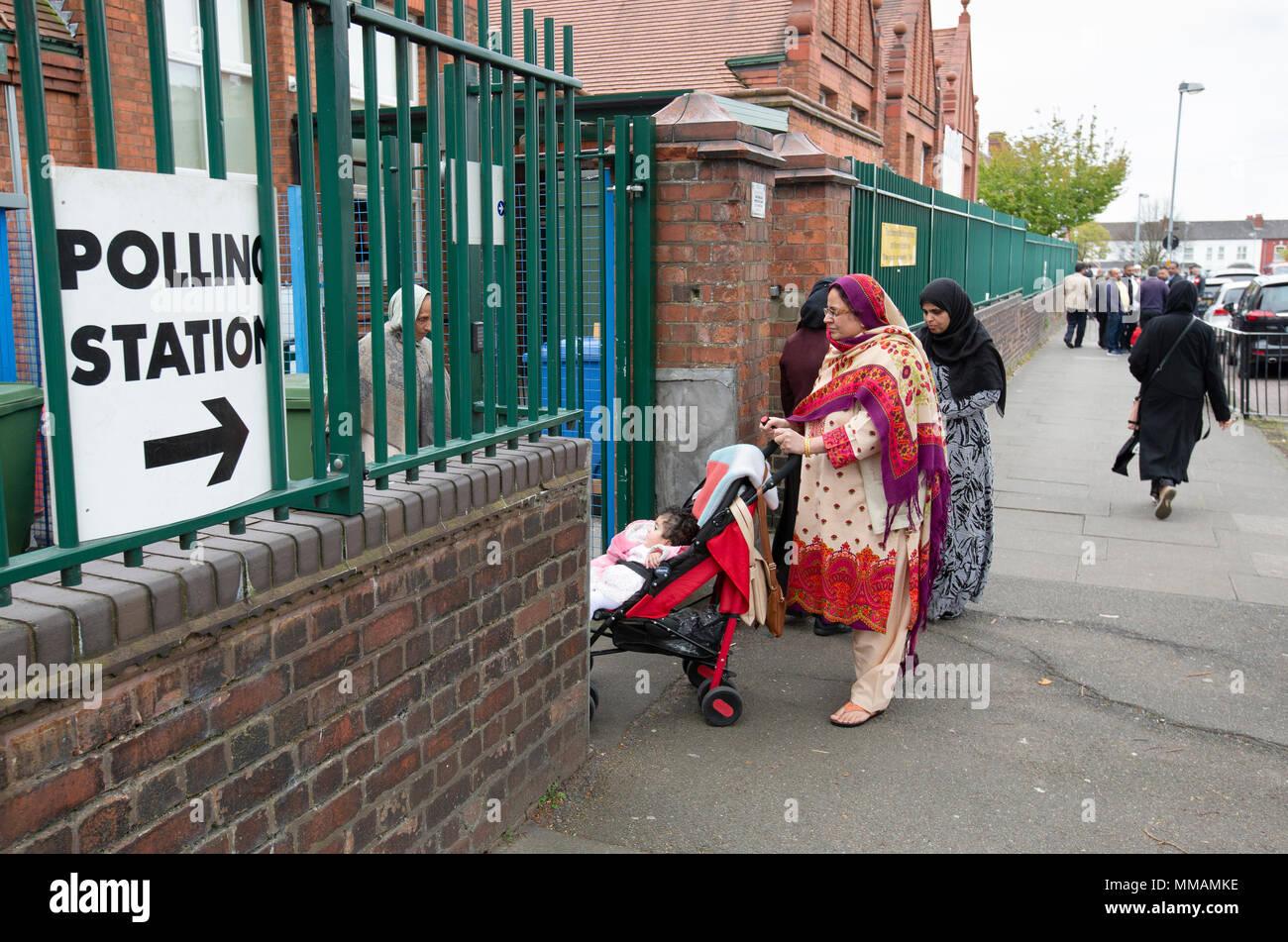 Los votantes musulmanes que llegan a un puesto de votación en Small Heath, Birmingham, para las elecciones locales en mayo de 2018. Imagen De Stock