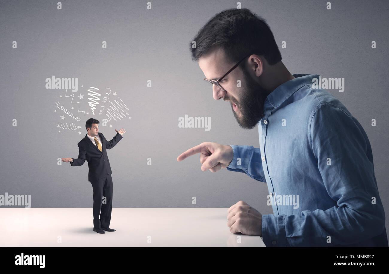 Profesional joven empresario estar enfadado con otro empresario en miniatura que tiene garabatos por encima de su cabeza Imagen De Stock