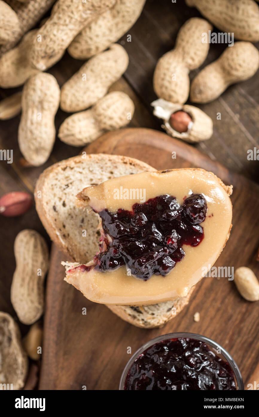 Sándwich de mantequilla de maní y mermelada sobre fondo de madera de estilo rústico. Saludable Desayuno casero. Imagen De Stock