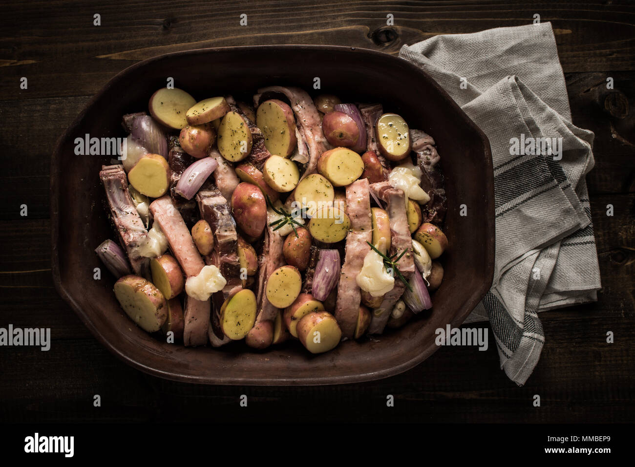 Chuletas de lomo de cordero con verduras en el plato de barro rústico preparado para asar. Copie el espacio. Imagen De Stock