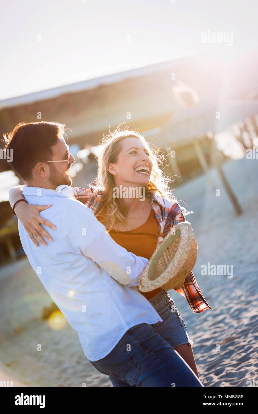 Verdaderamente feliz pareja juguetona divirtiéndose en la playa Imagen De Stock