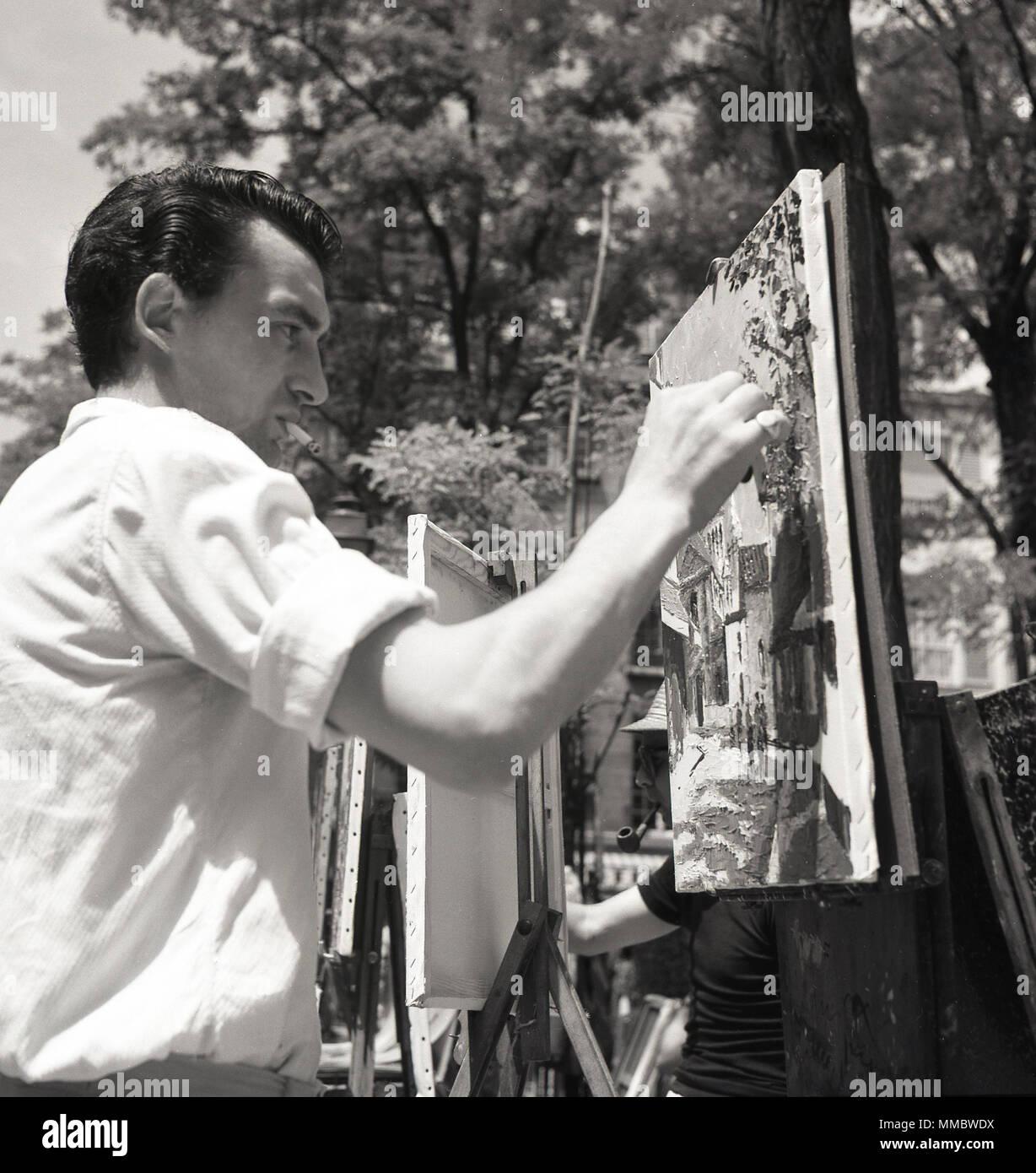 1950, foto histórica, un artista callejero masculino pintura sobre un lienzo afuera, en la Place du Tertre, una plaza a Montmartre en París, Francia, famosa por sus artistas y su historia artística. Imagen De Stock